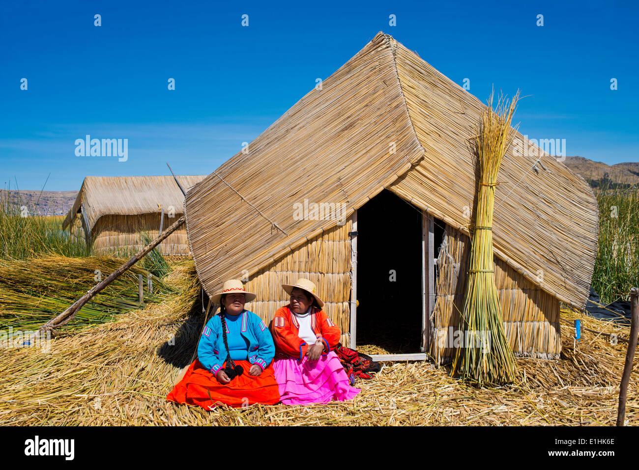 Due donne di Uro indiani indossando vestiti tradizionali seduti davanti ad una capanna di reed, isole galleggianti Foto Stock