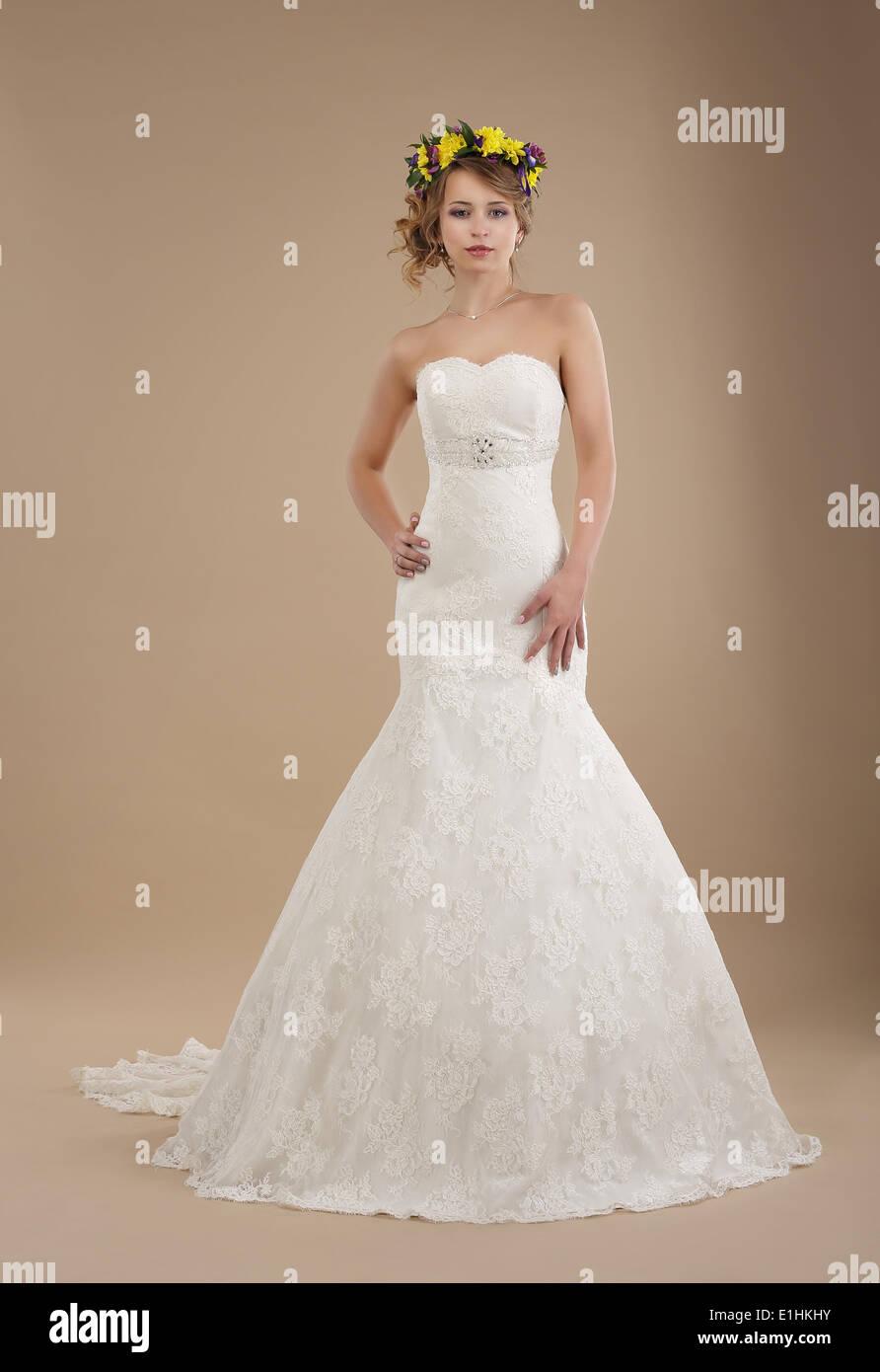 Incantevole donna in abito da sposa con ghirlanda di fiori Immagini Stock