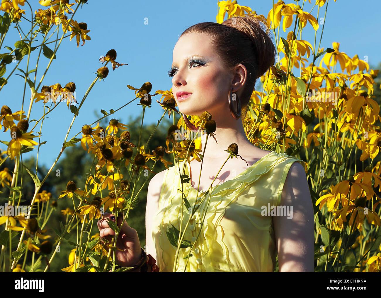 Durante l'estate. Giovani femmine in Prato tra fiore fiori giallo Immagini Stock