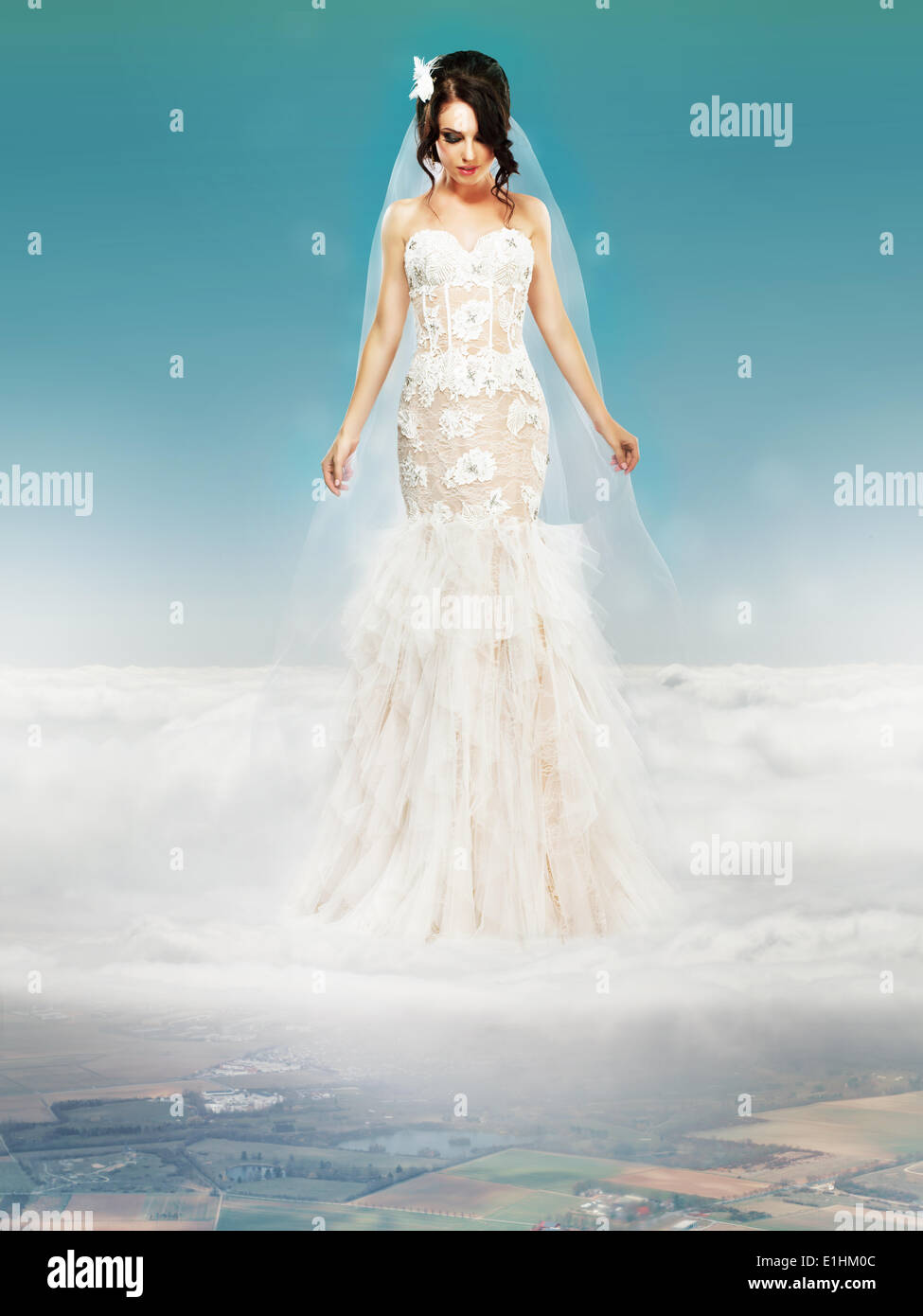 Sposa matrimonio abito bianco in piedi su una nuvola e guardando a terra Immagini Stock