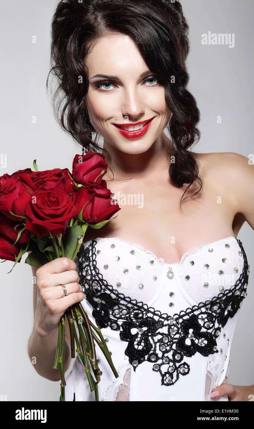 La fragranza. Bella giovane donna Holding bouquet di rose rosse. Il giorno di San Valentino Immagini Stock