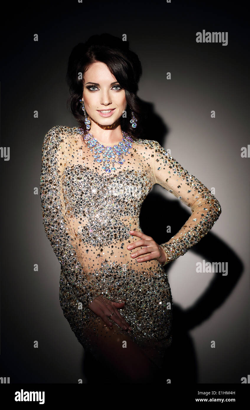 Glam. Donna di successo in argento abito da sera su nero Immagini Stock