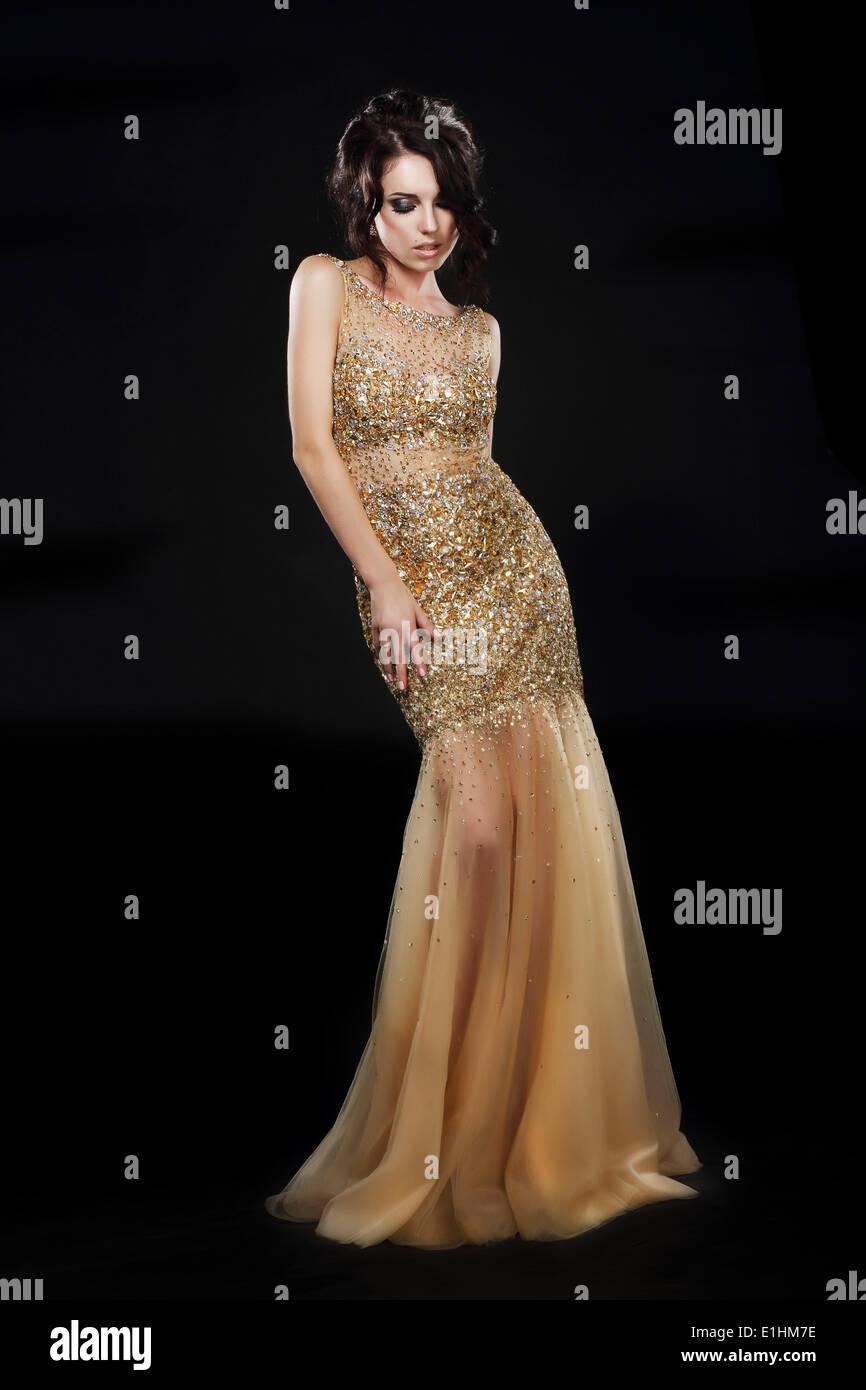 Vogue. Bellissimo modello di moda in abito Golden-Yellow su nero Foto Stock