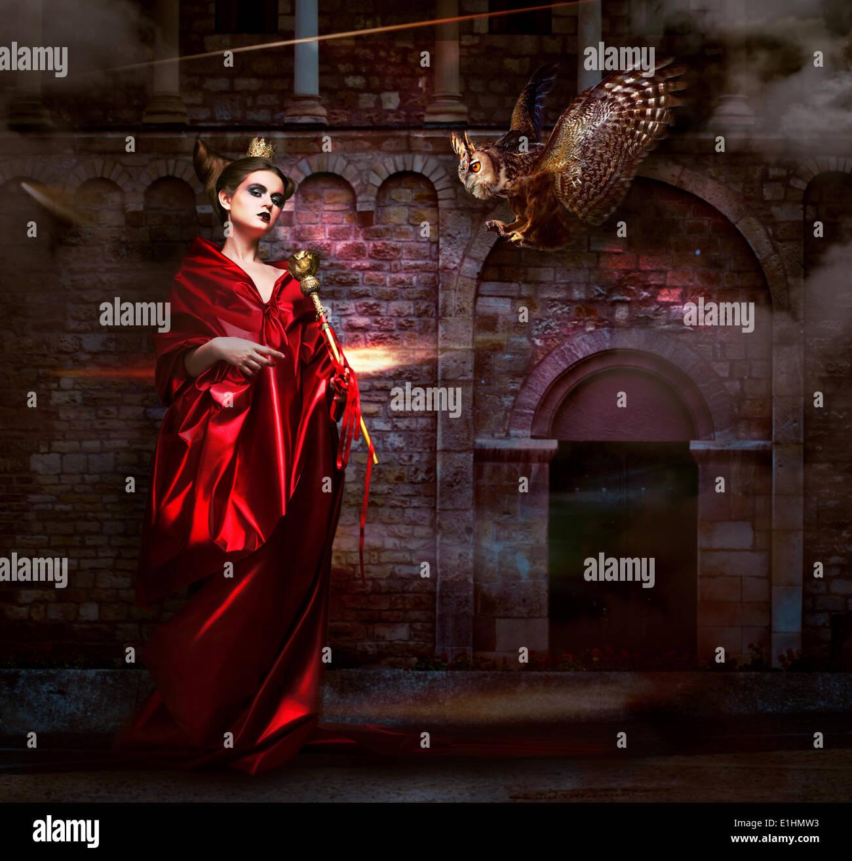 Il misticismo. La stregoneria. Stregone in rosso manto con Vulture - Hawk. Antico Castello spaventoso Immagini Stock