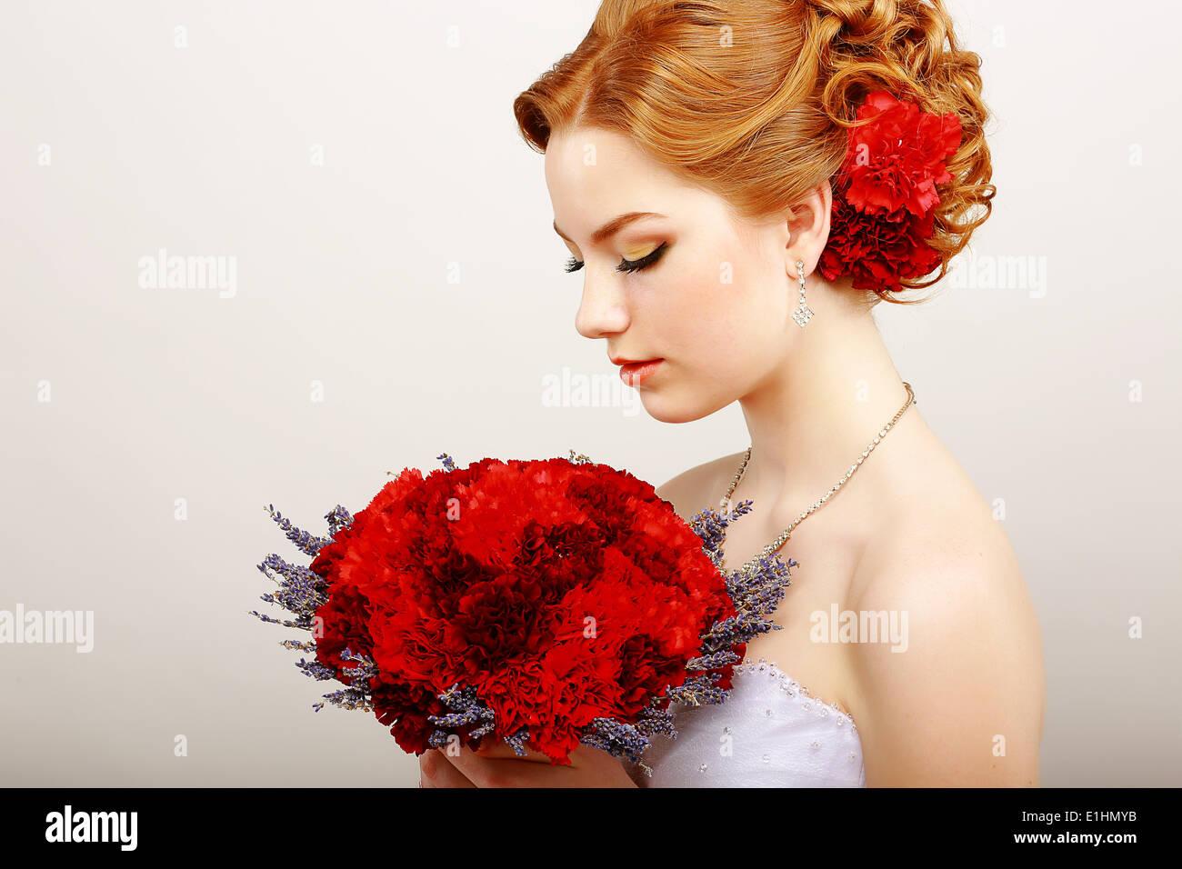 Mitezza. Profilo di calma Donna rosso con bouquet di fiori. Tranquillità e dolcezza Foto Stock