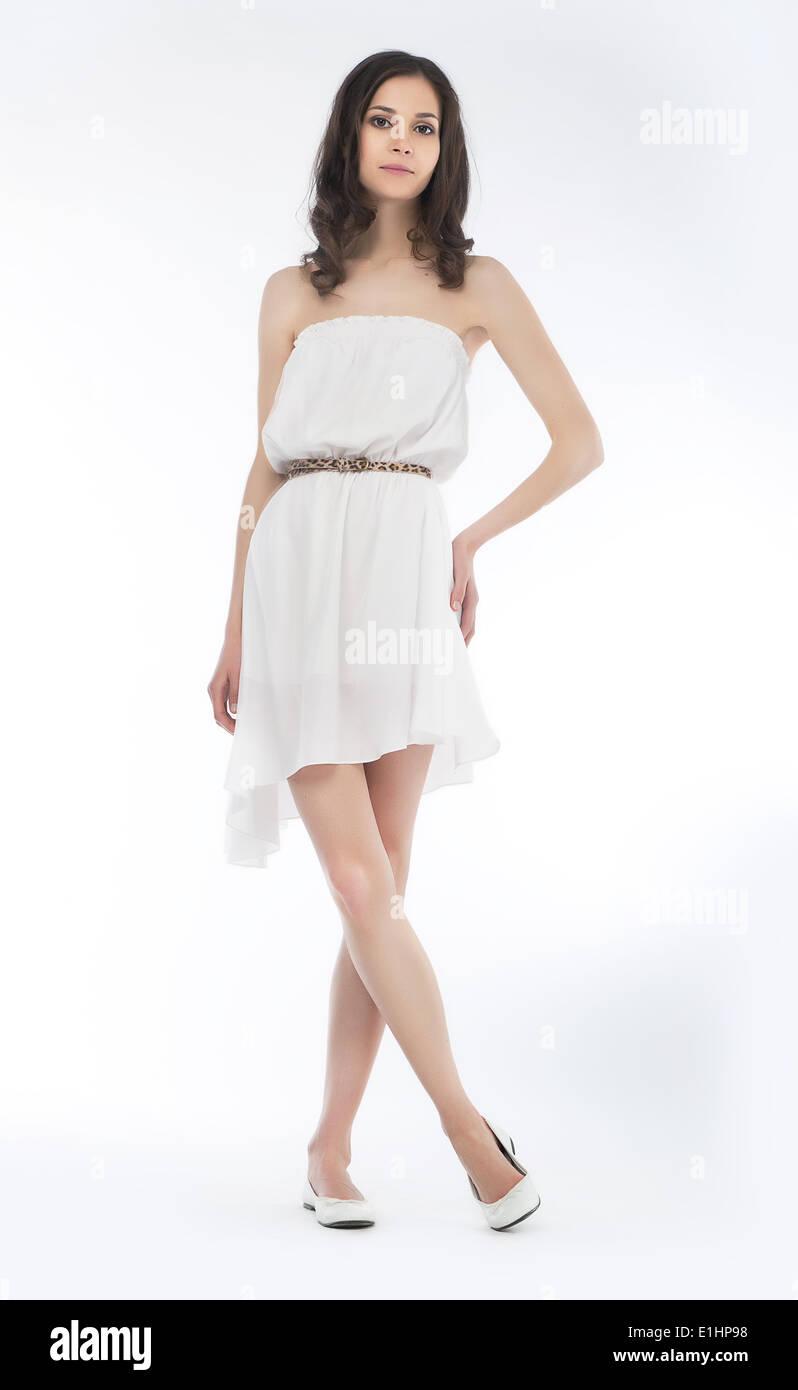 27997e21d871 Giovane donna affascinante in abiti estivi in posa su sfondo bianco  Immagini Stock