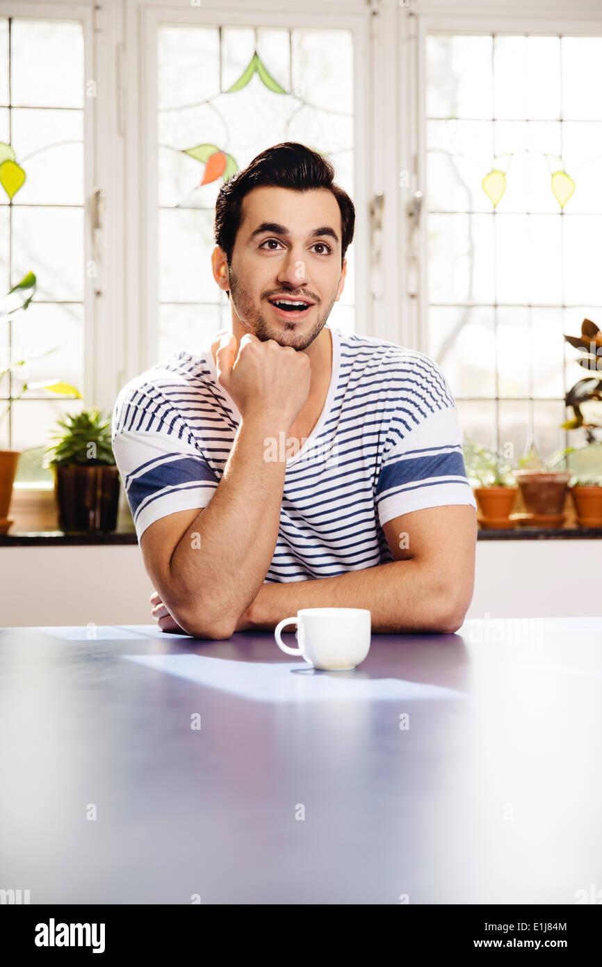 Ritratto di stupito giovane uomo seduto al tavolo blu con una tazza Immagini Stock