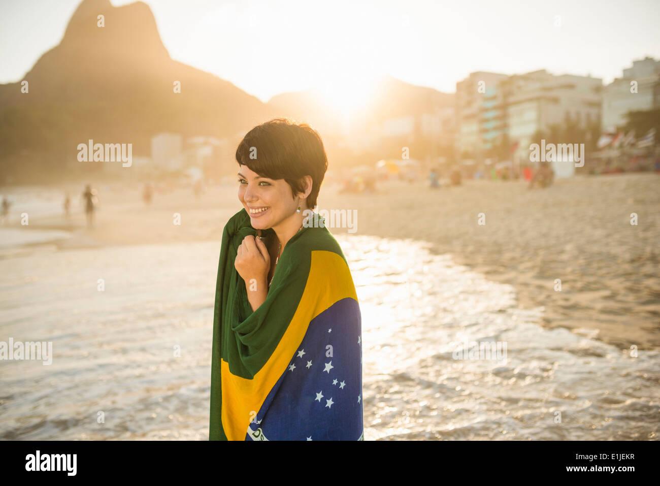Giovane donna avvolta nella bandiera brasiliana, la spiaggia di Ipanema, Rio, Brasile Immagini Stock