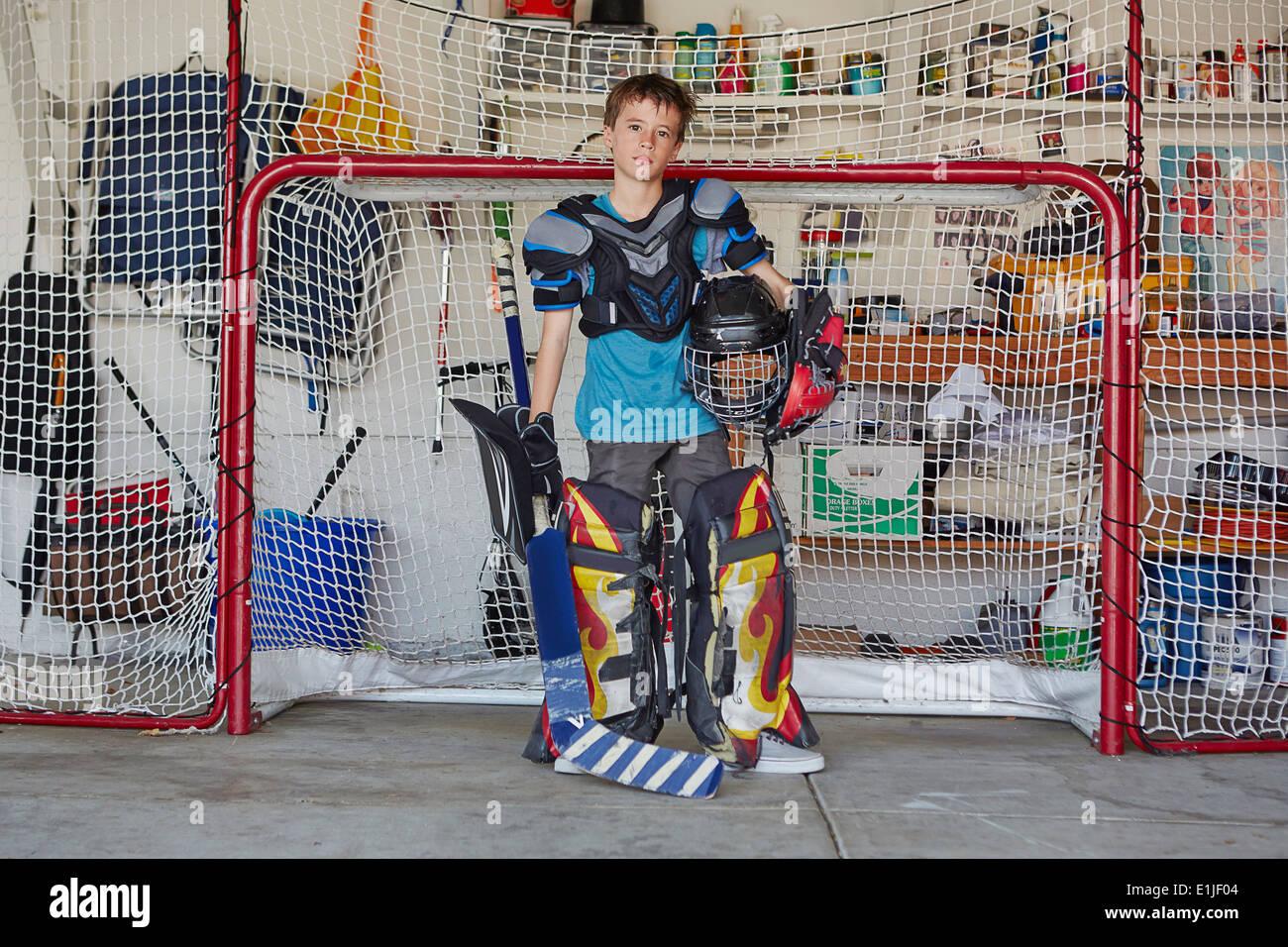 Ragazzo in obiettivo di hockey di indossare abbigliamento protettivo Immagini Stock