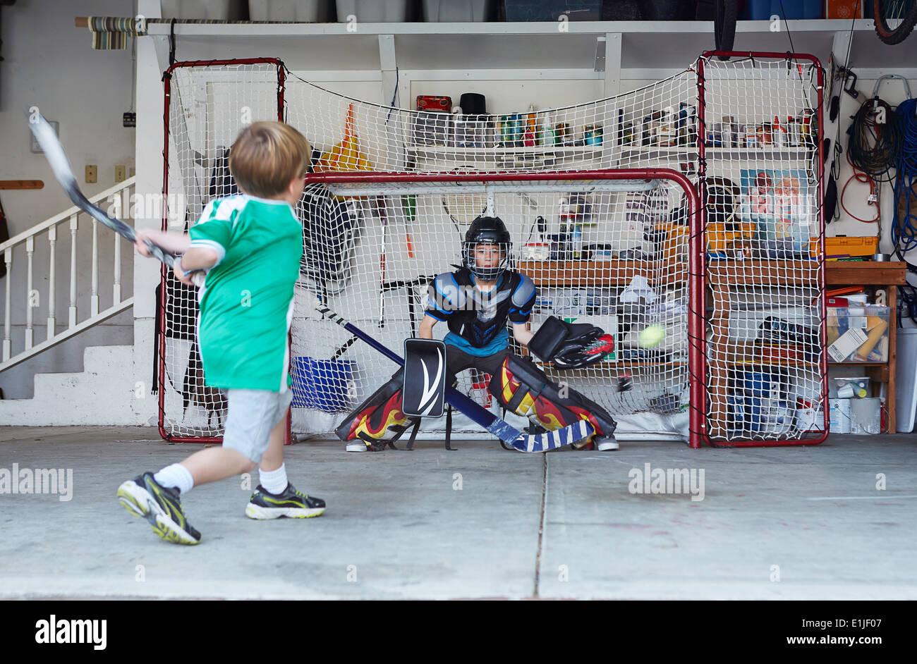 Ragazzi giocare ad hockey in garage Immagini Stock