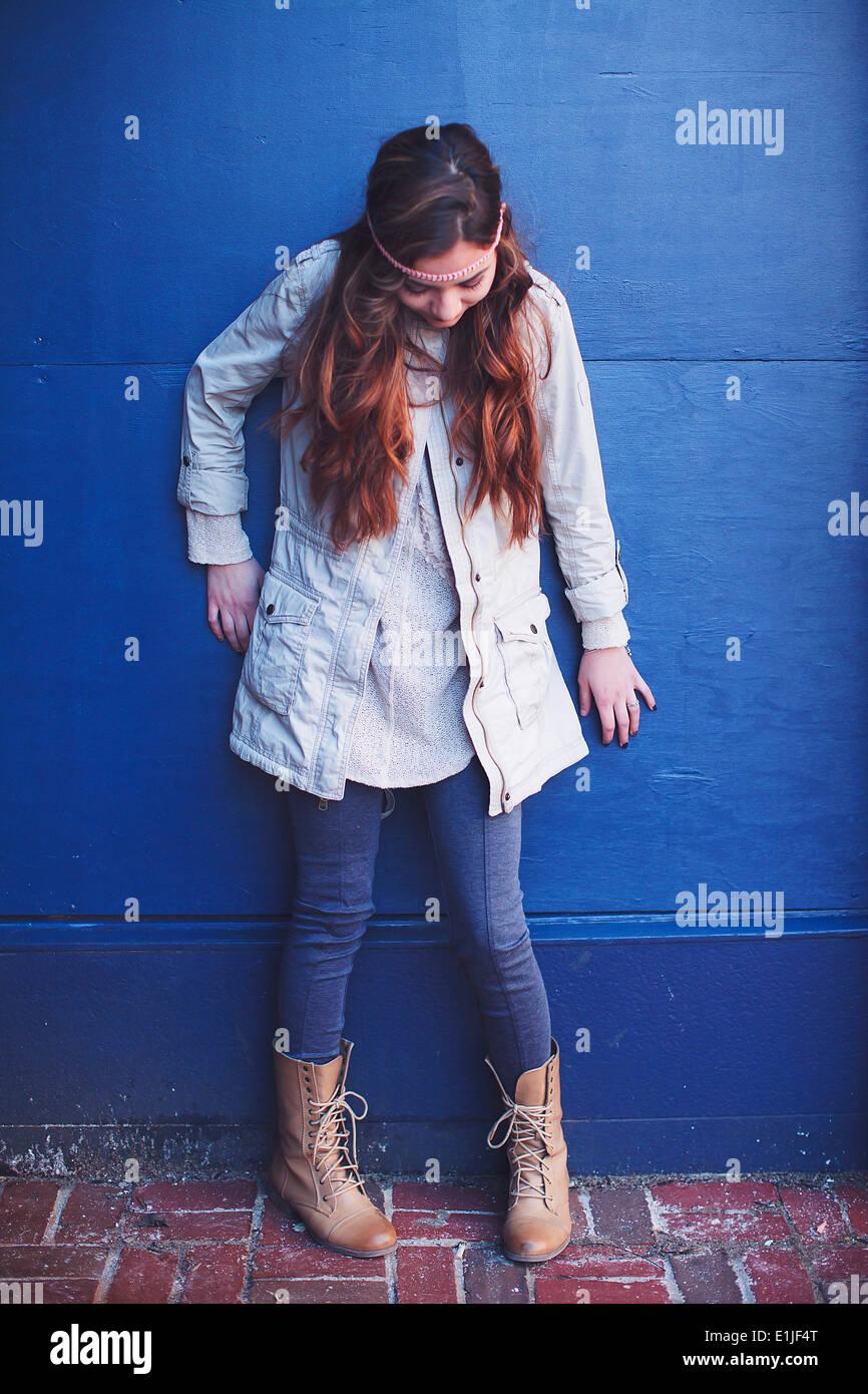 Giovane donna appoggiata contro la parete blu guardando verso il basso Immagini Stock