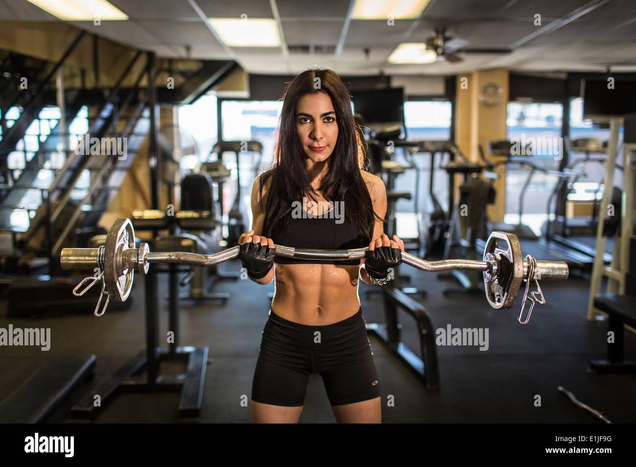 Ritratto di metà donna adulta il sollevamento pesi in palestra Foto Stock