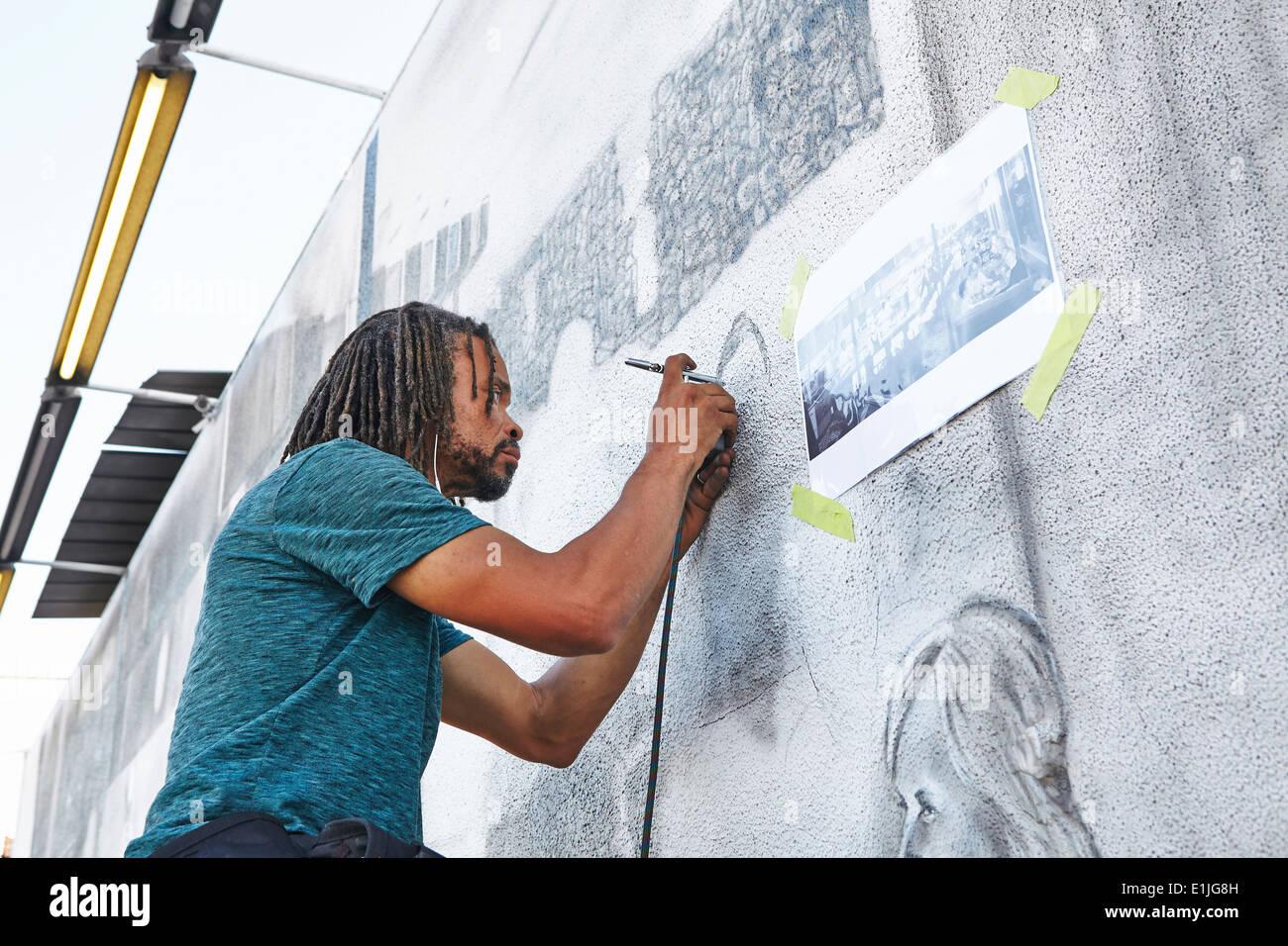 Maschio americano africano aerografo artista pittura murale Immagini Stock