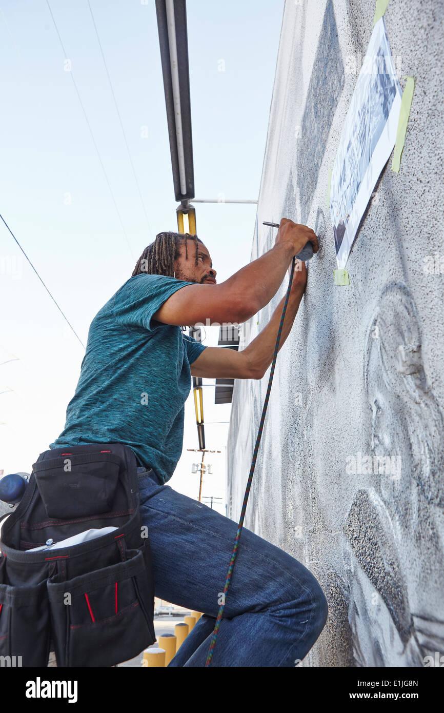 Maschio americano africano aerografo artista pittura murale a parete Immagini Stock