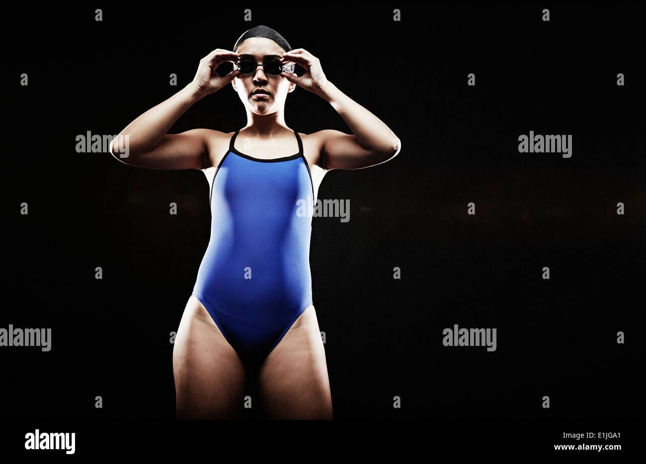 Giovane donna di indossare il costume da bagno blu a mettere su gli occhiali di protezione Immagini Stock