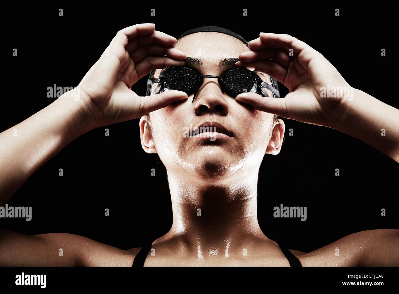 Giovane donna mettendo su occhiali da nuoto Immagini Stock