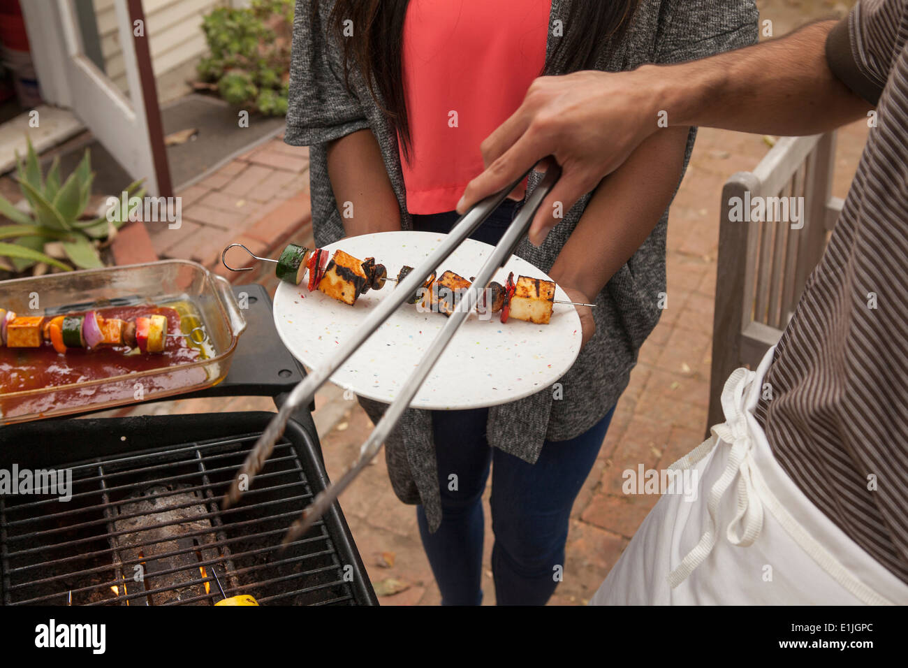 Uomo di cottura spiedini vegetali su barbecue Immagini Stock