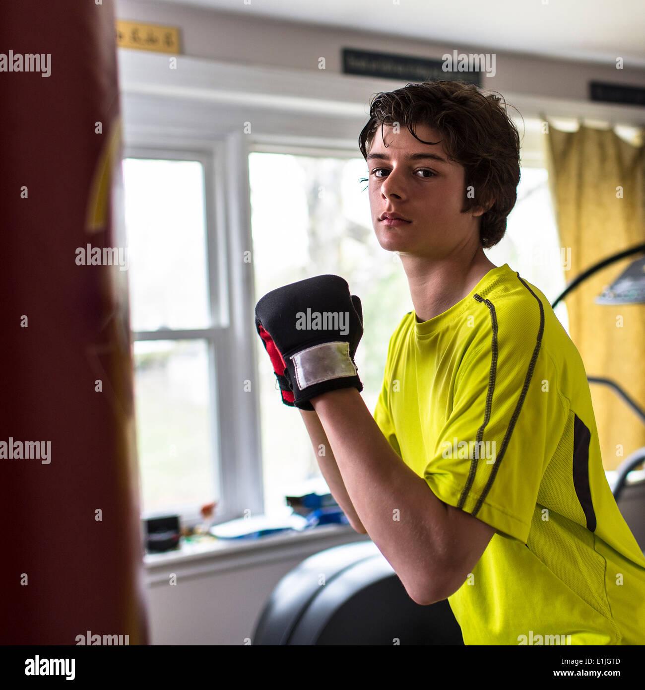 Ragazzo adolescente che indossa guantoni da pugilato Immagini Stock