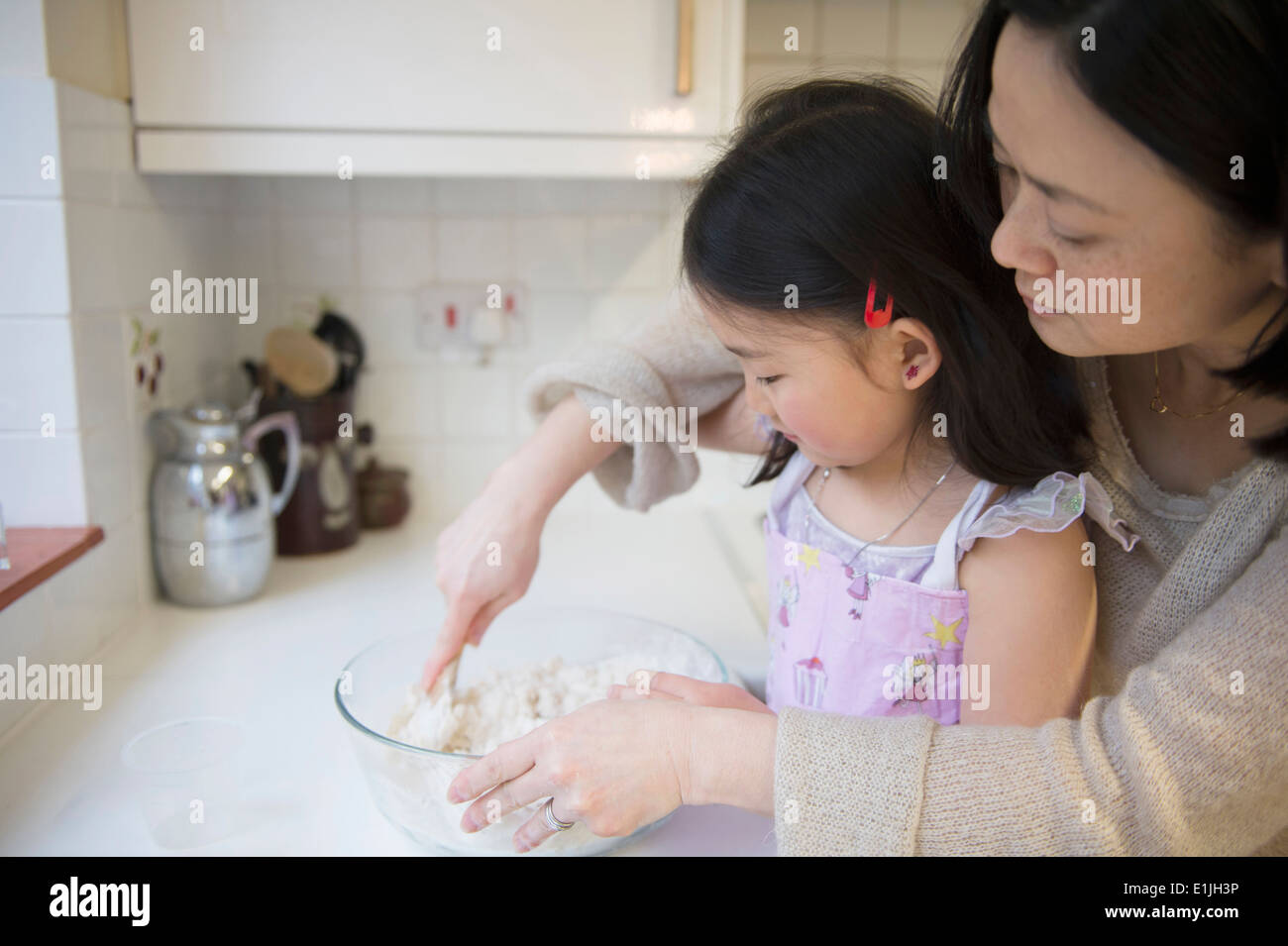 Madre e figlia in cucina, la miscelazione degli ingredienti nel recipiente Immagini Stock
