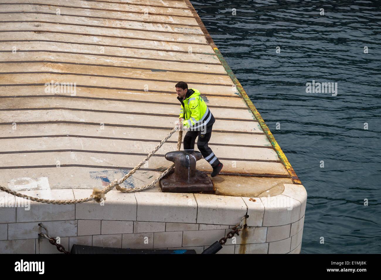 Un uomo getta fuori una corda dal suo posto barca Immagini Stock