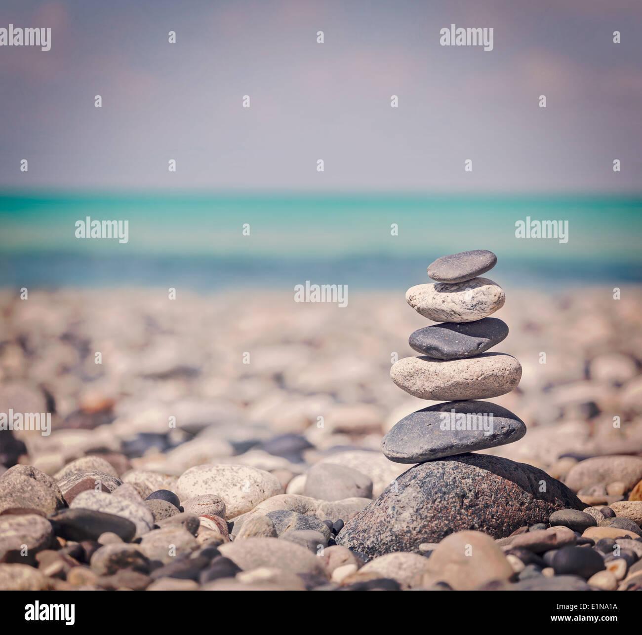 Vintage retrò hipster stile immagine di viaggio di meditazione Zen sfondo - pietre equilibrata pila vicino sul mare spiaggia Immagini Stock