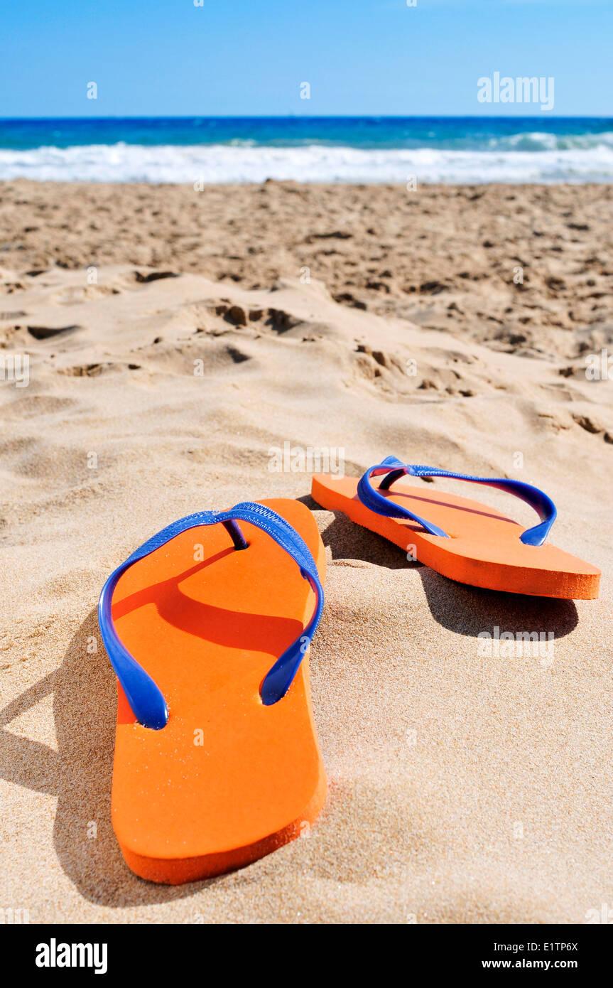 Una coppia di orange flip-flop sulla sabbia di una spiaggia Immagini Stock