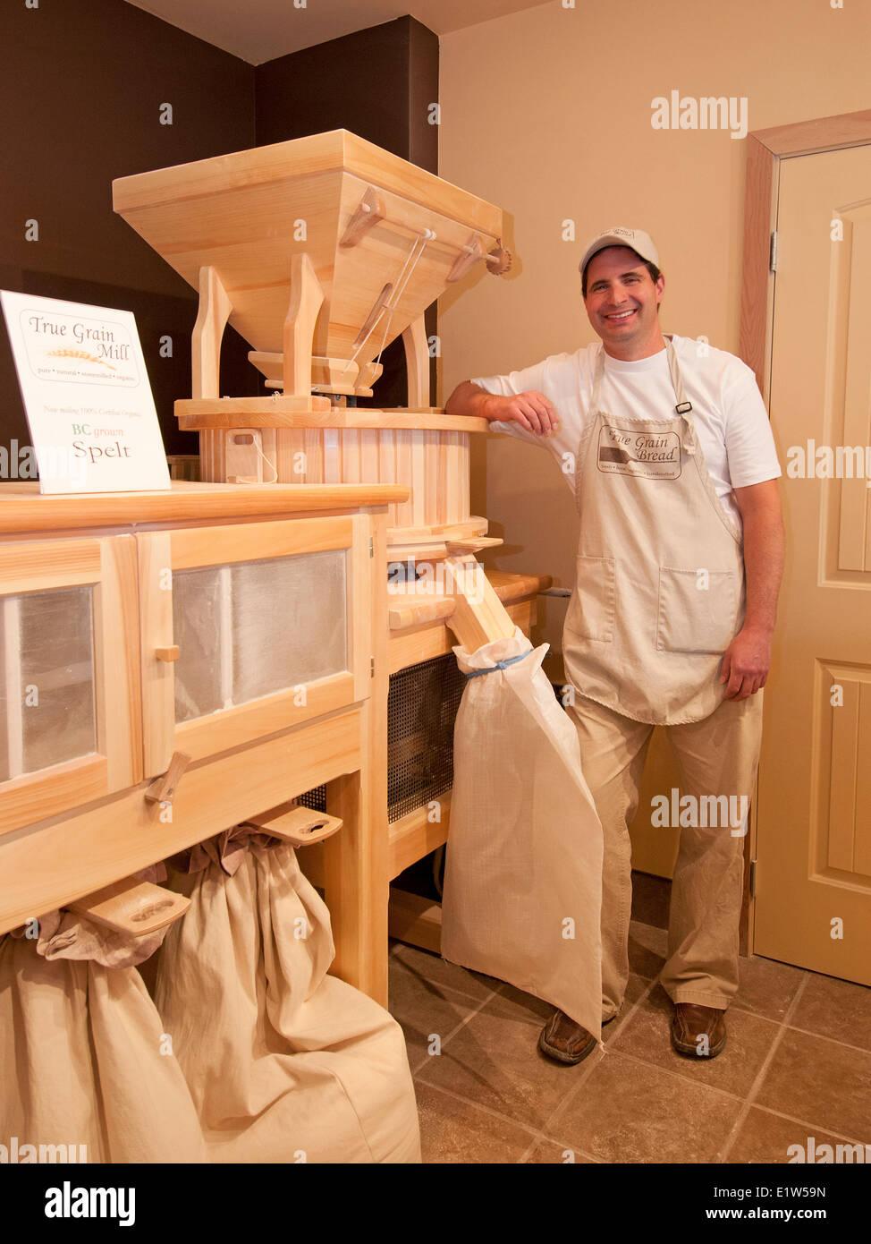 Il proprietario del vero pane di grano in Summerland, British Columbia sta con il suo mulino di farina, regione Immagini Stock