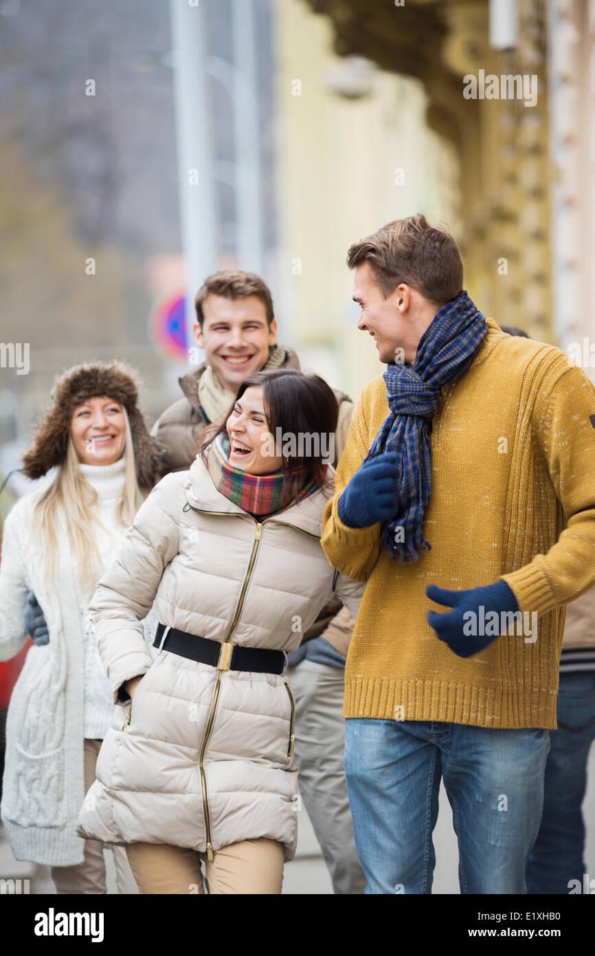 Allegro coppie giovani in abiti caldi sulla strada di città Immagini Stock