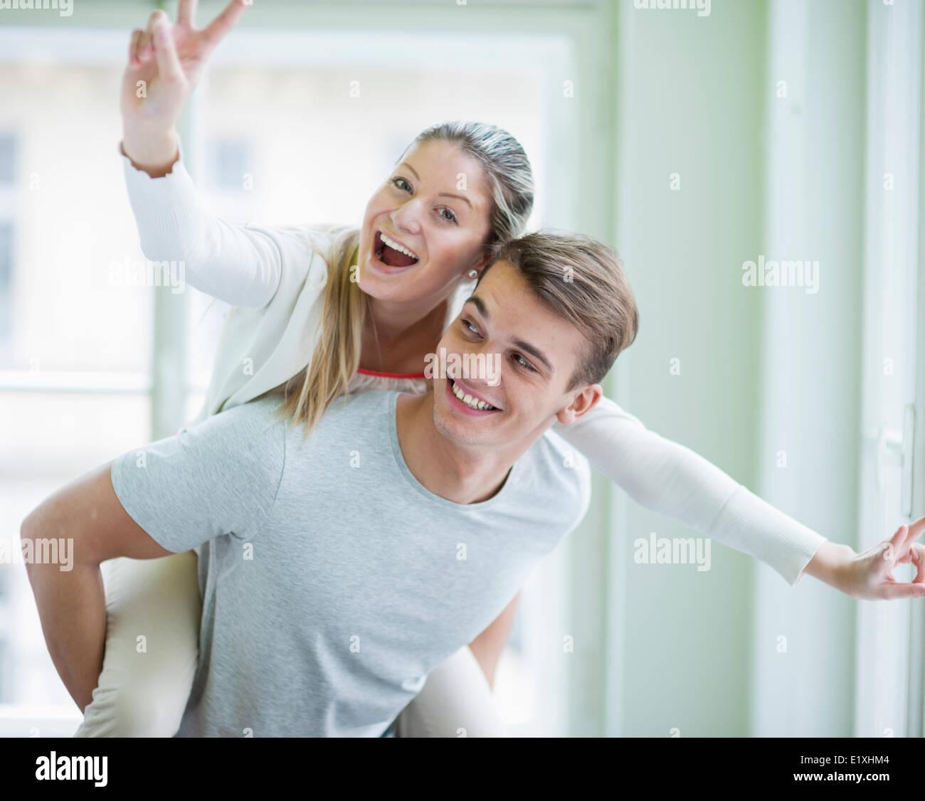 Ritratto di donna felice godendo piggyback ride dato da uomo a casa Immagini Stock