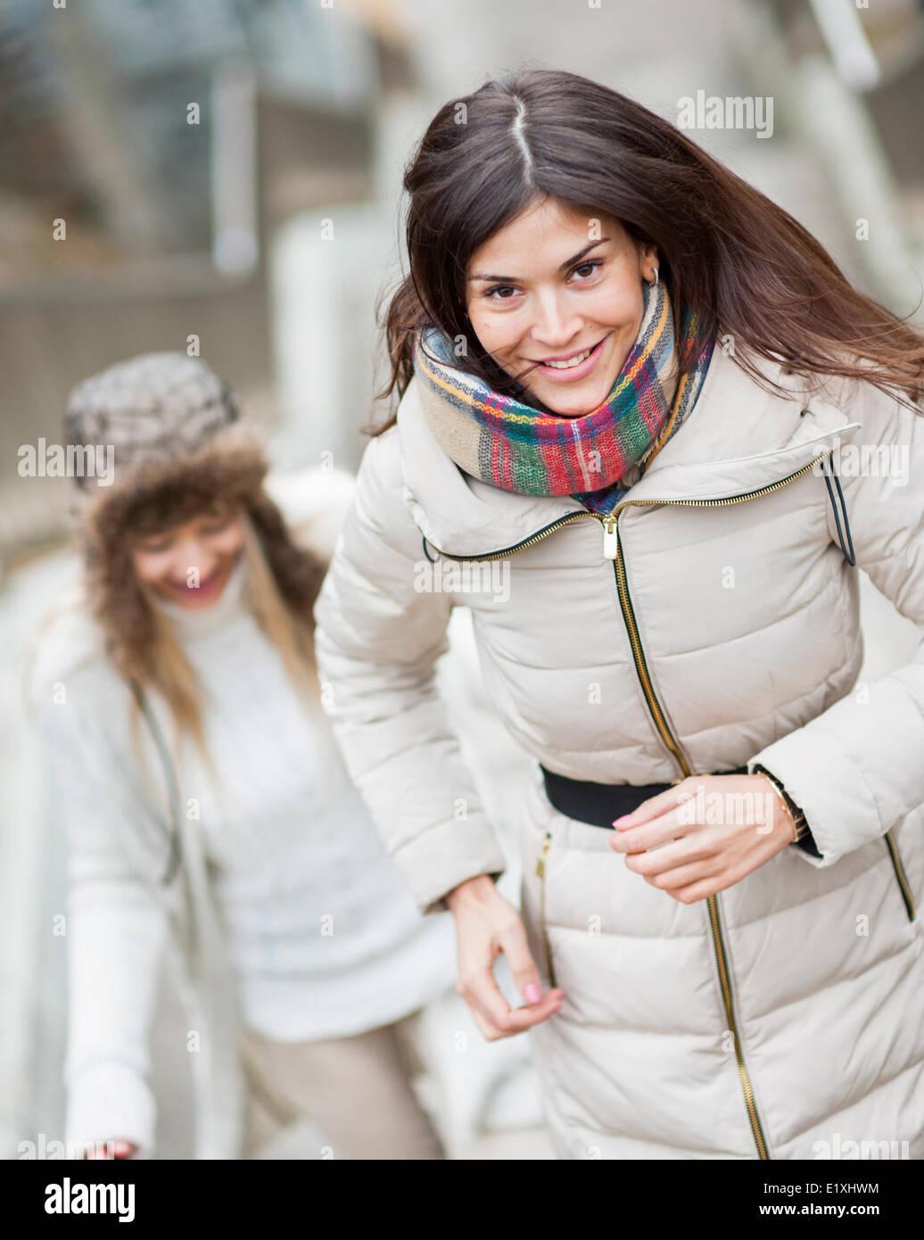 Sorridente giovane donna a salire le scale con un amico all'aperto Immagini Stock