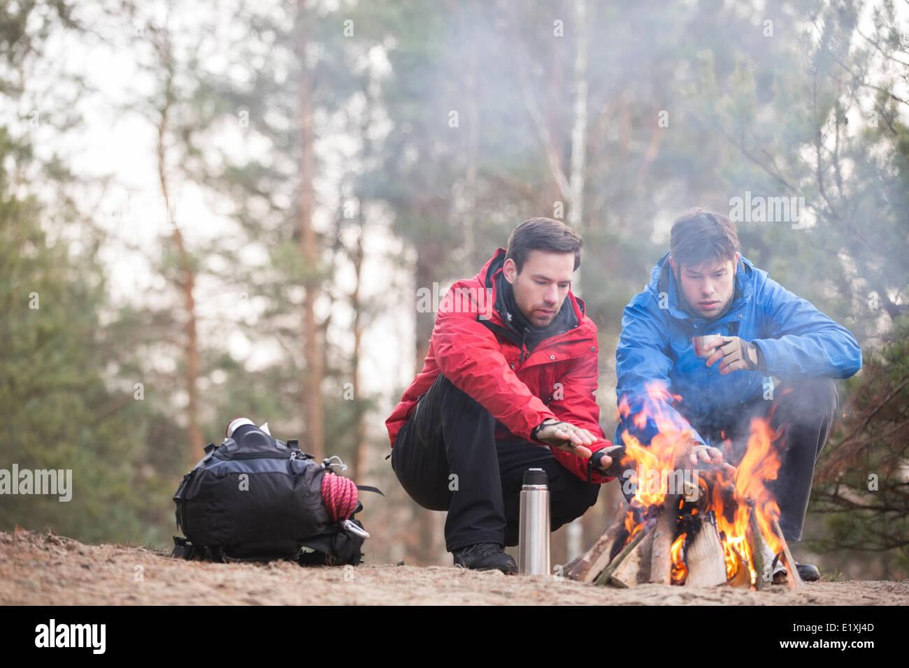 Gli escursionisti maschio mani di riscaldamento a fuoco nella foresta Immagini Stock