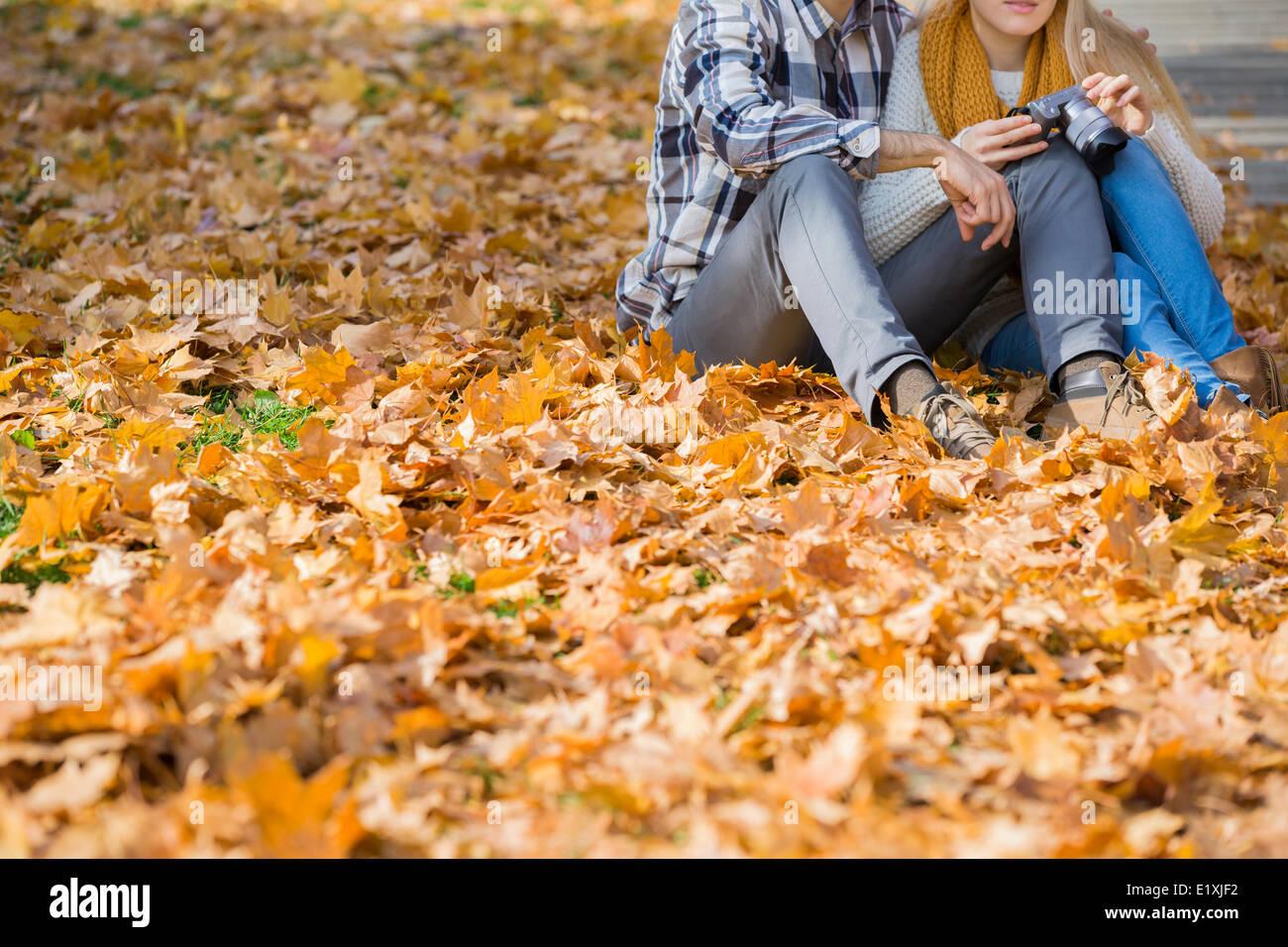 Sezione bassa del giovane con fotocamera seduto su foglie di autunno nel parco Immagini Stock