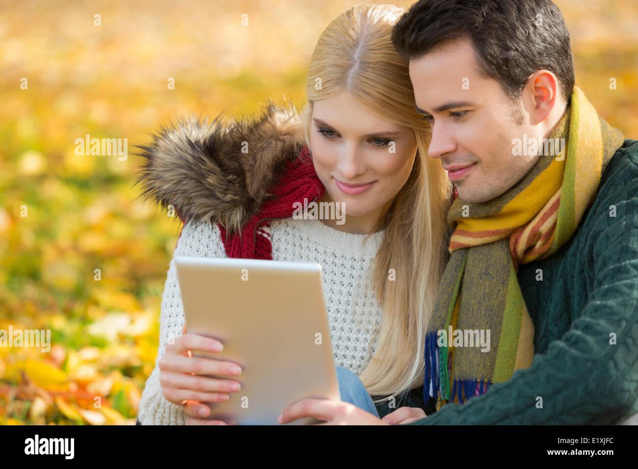 Paio utilizzando digitale compressa nel parco durante l'autunno Immagini Stock