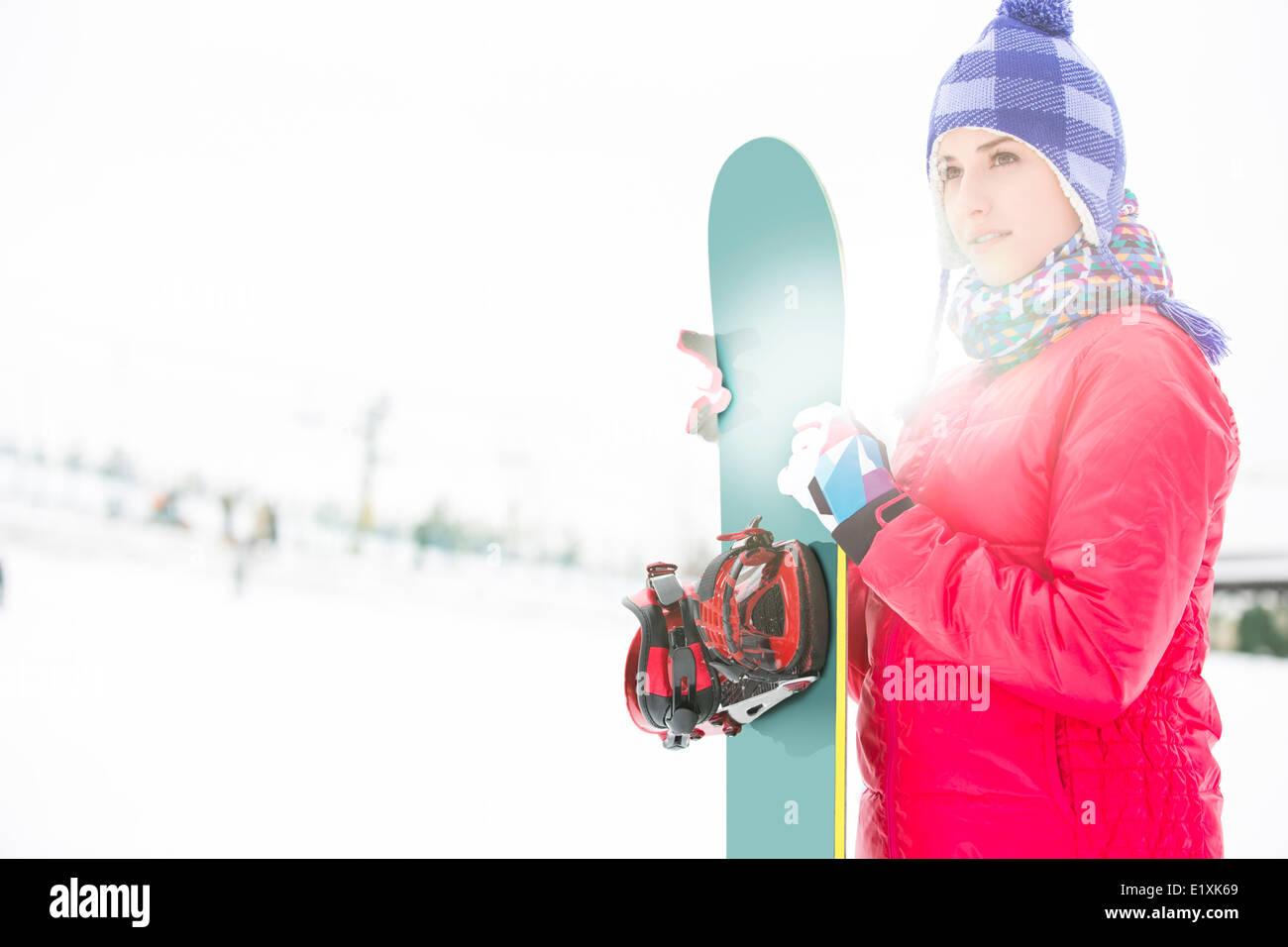 Bella giovane donna in abiti caldi holding snowboard durante la stagione invernale Immagini Stock
