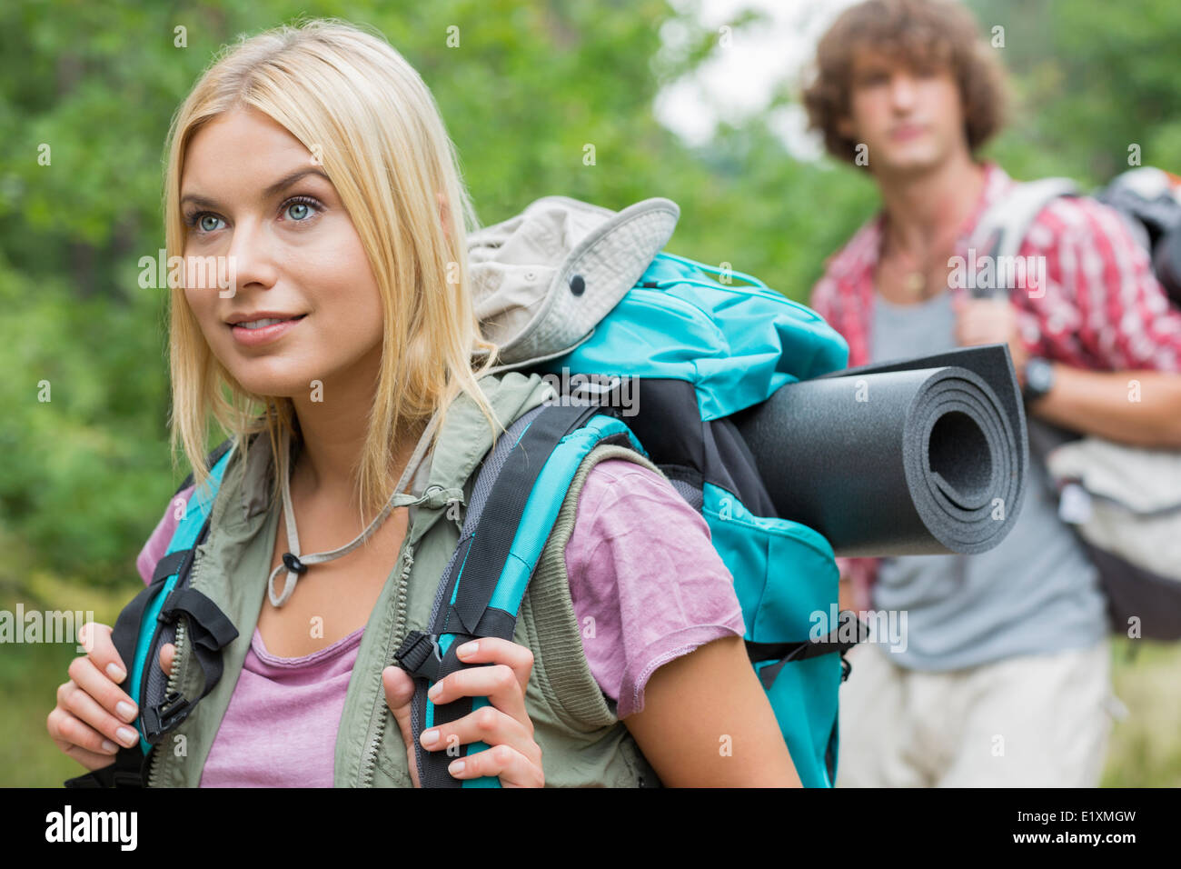 Bellissima femmina backpacker che guarda lontano con uomo in background in foresta Immagini Stock