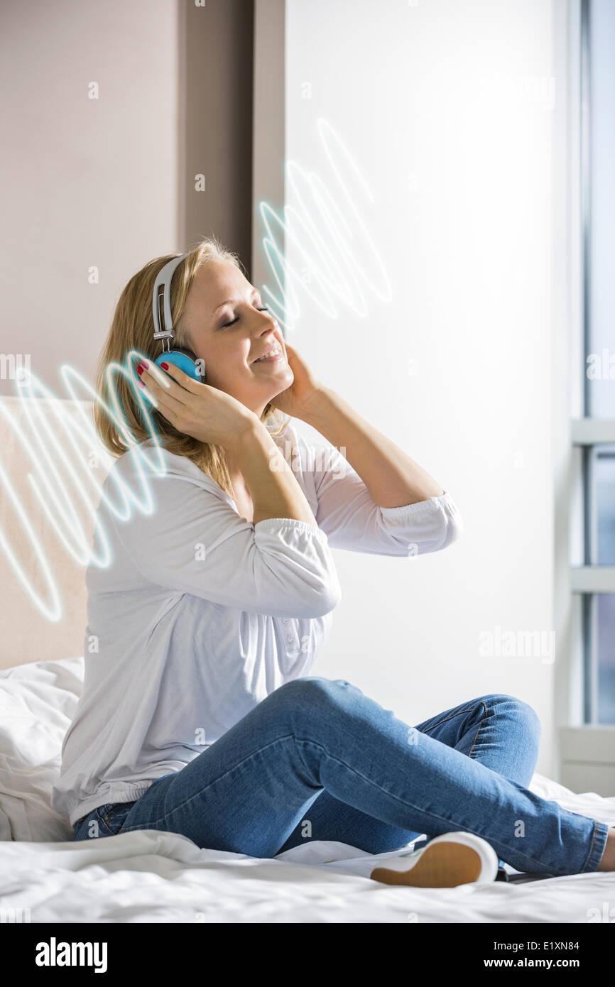 Rilassata metà donna adulta ascoltando la musica attraverso le cuffie sul letto Immagini Stock