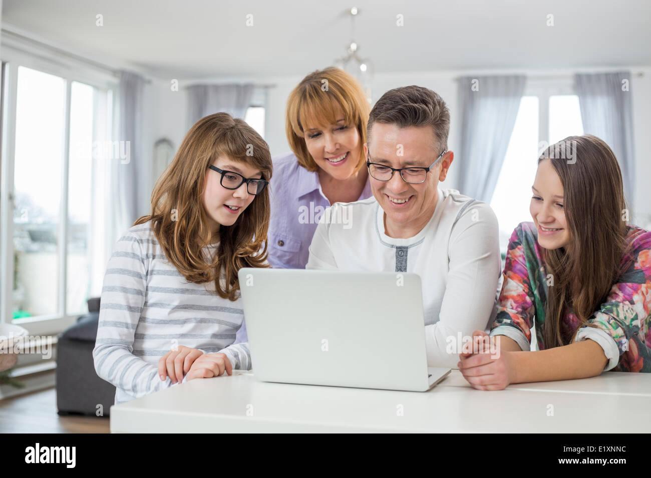 Famiglia di quattro utilizzando laptop insieme a tavola in casa Immagini Stock