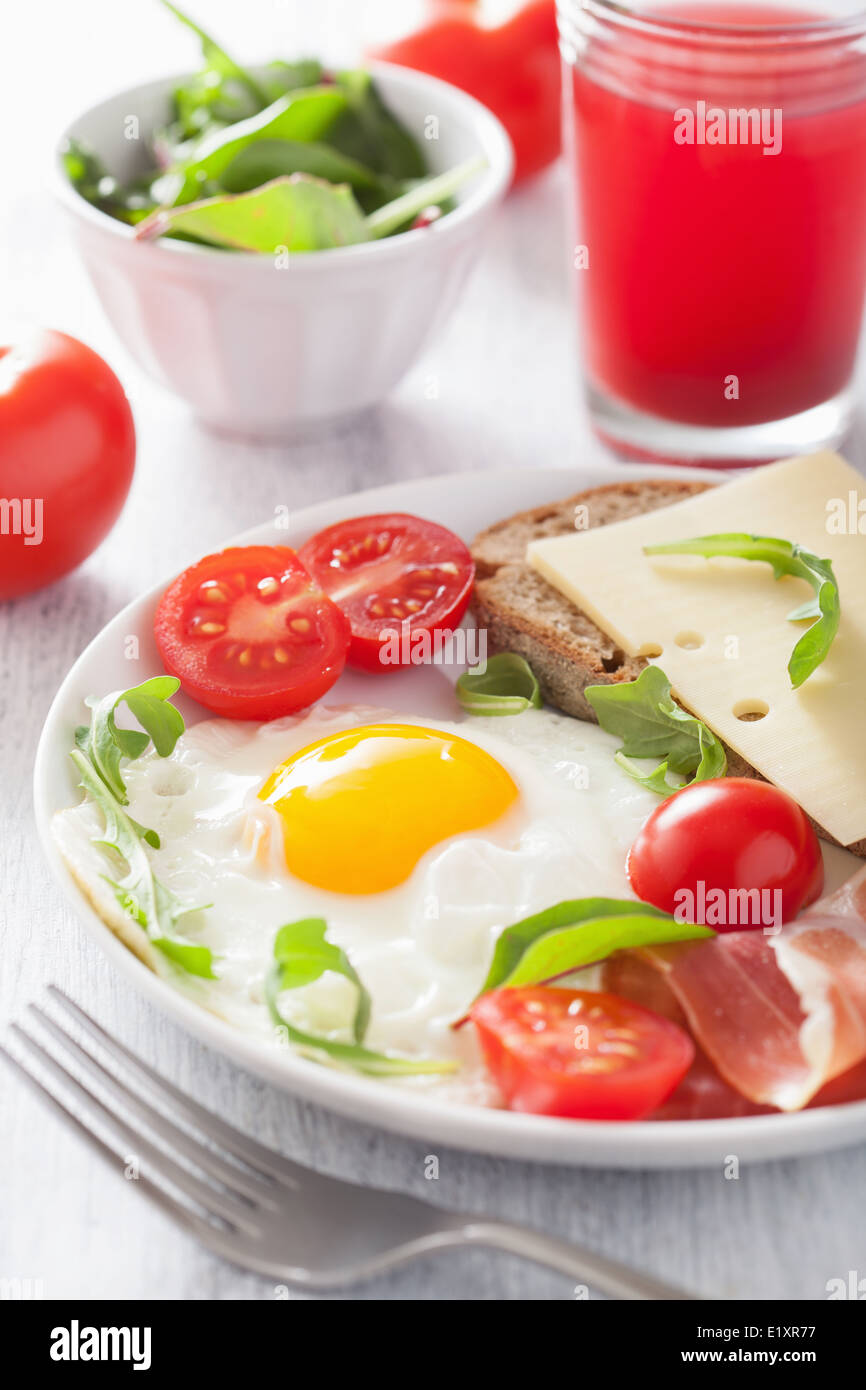 Uovo fritto prosciutto pomodori per la sana prima colazione Immagini Stock