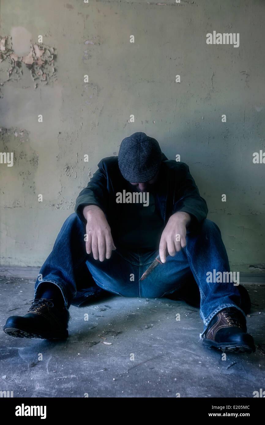 Un uomo con un coltello seduta sul pavimento in una casa abbandonata Foto Stock