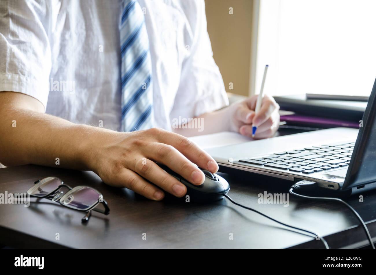 Le mani di imprenditore tenendo una penna e un mouse vicino al laptop Immagini Stock
