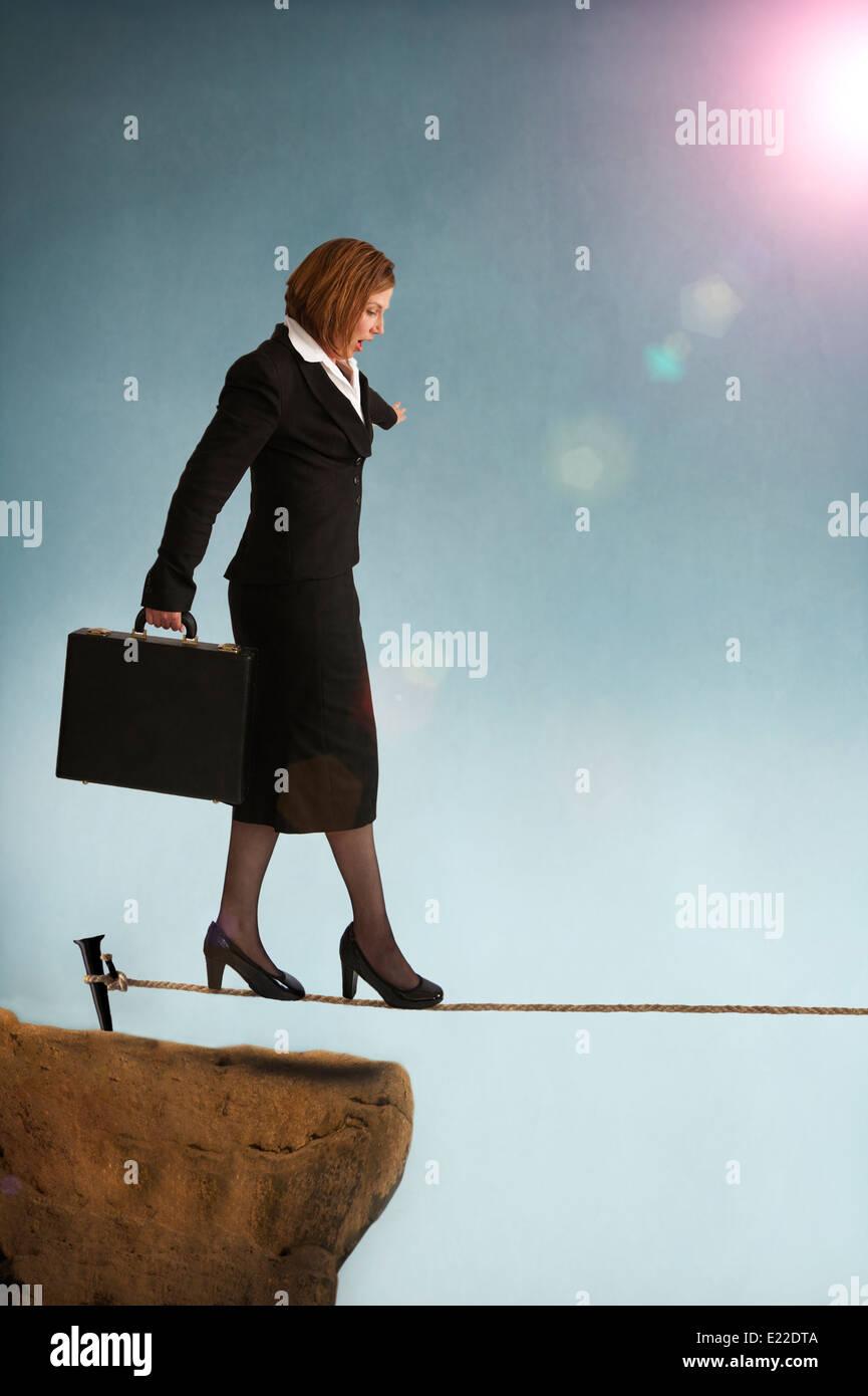 Imprenditrice a partire su una fune o highwire che illustra il concetto di rischio del business Immagini Stock