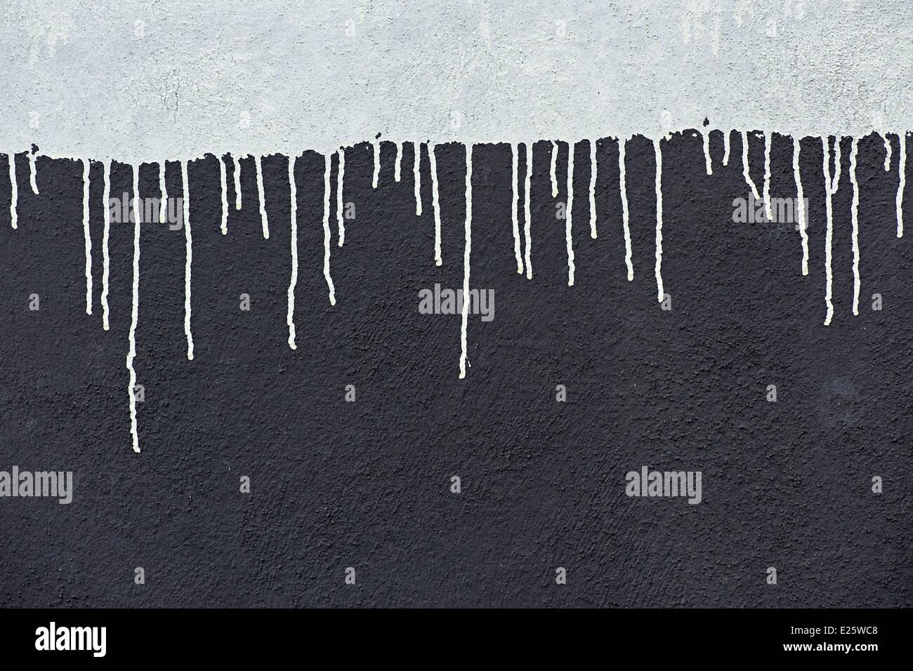 Vernice grigio scende al buio su un muro grigio Immagini Stock