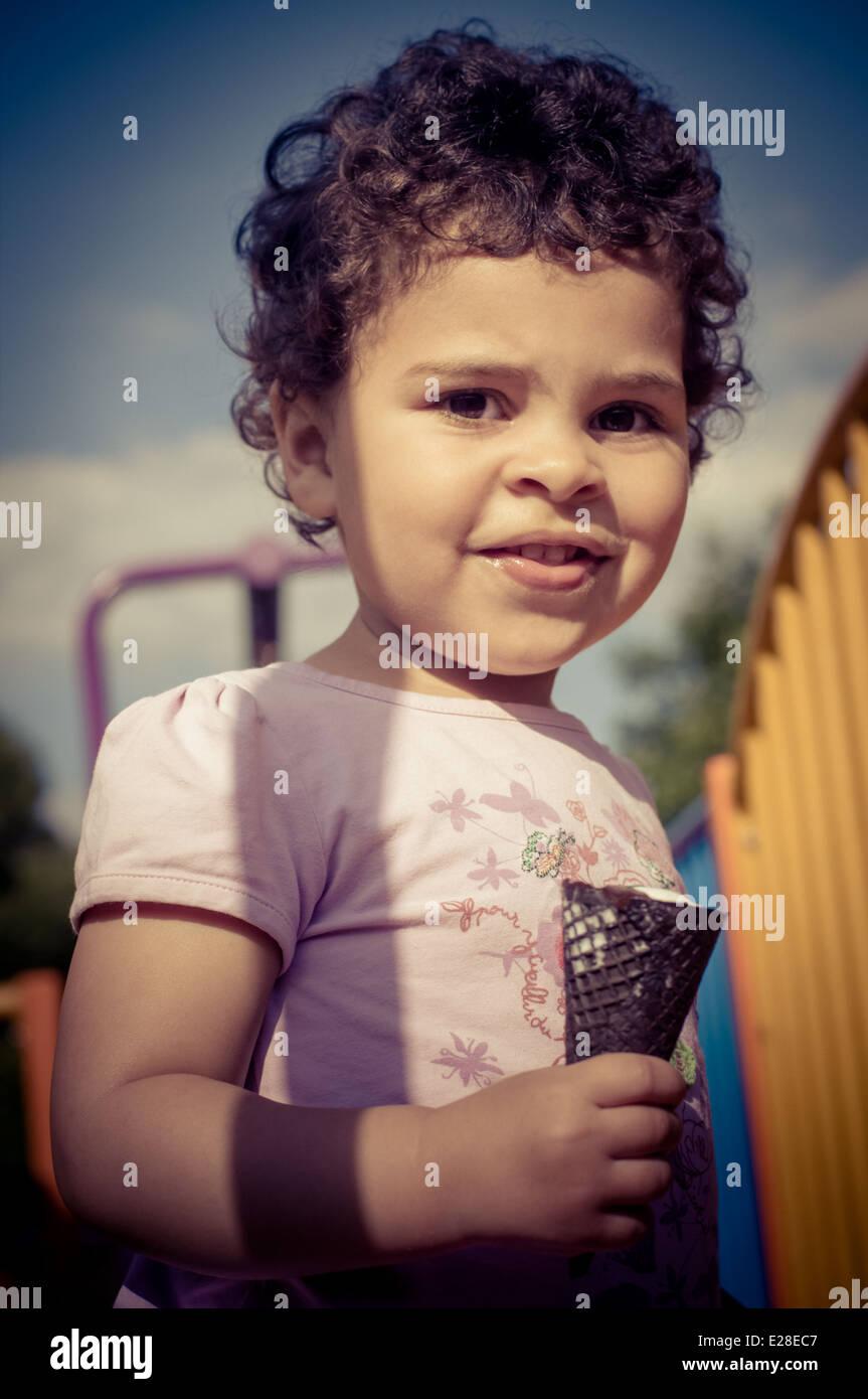 Il Toddler (2-3) nel parco giochi mentre mangiare un gelato Immagini Stock
