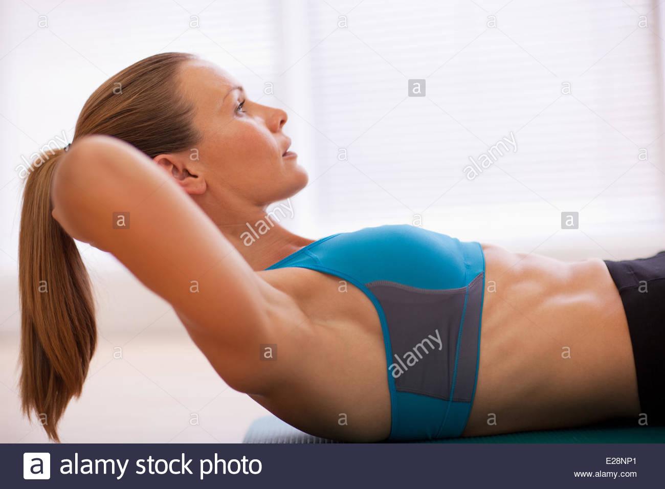 Donna gravi nel reggiseno sportivo facendo sit ups sul tappeto di esercizio Immagini Stock