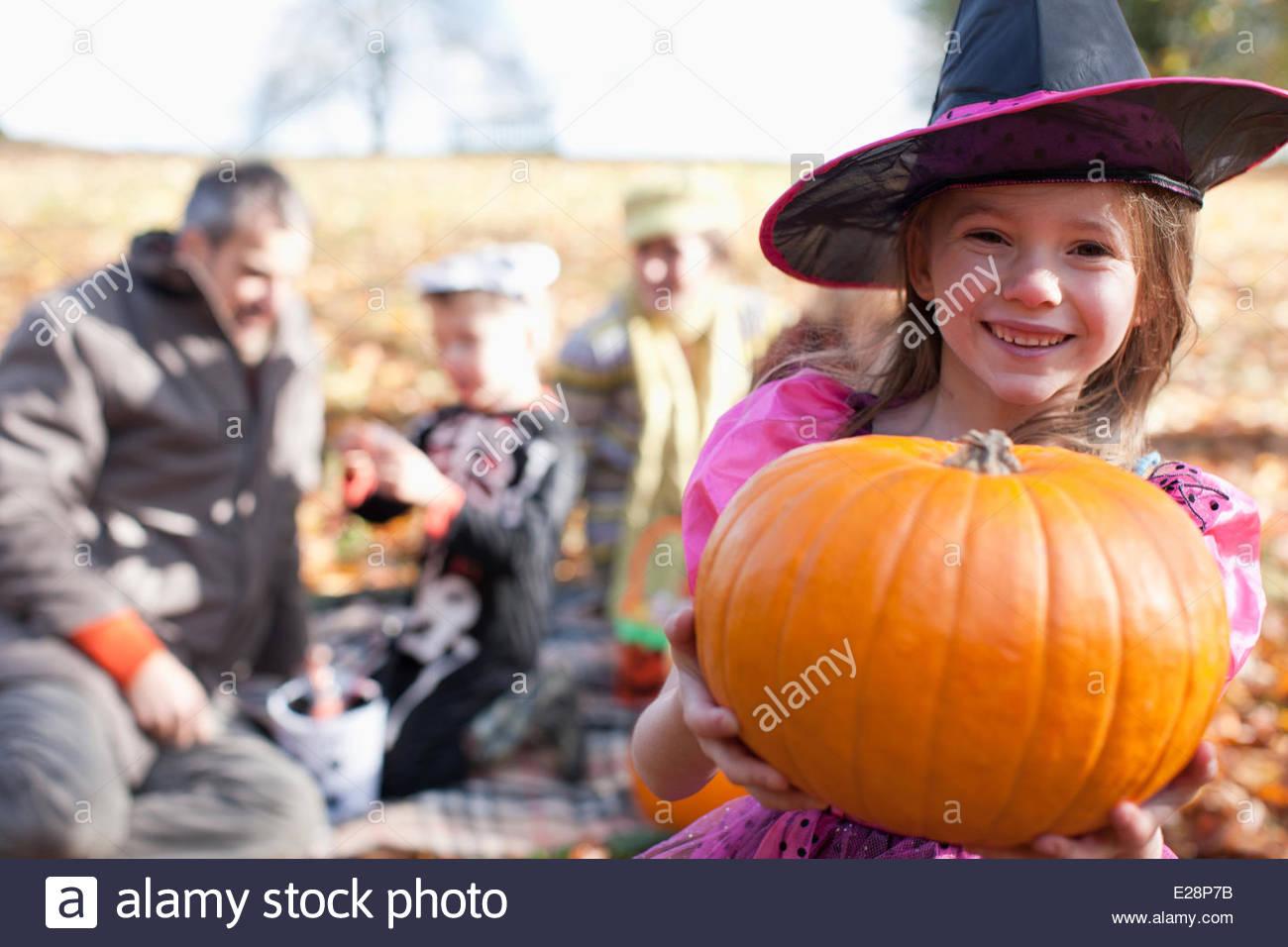 La Ragazza di Halloween costumi di zucca di contenimento Immagini Stock