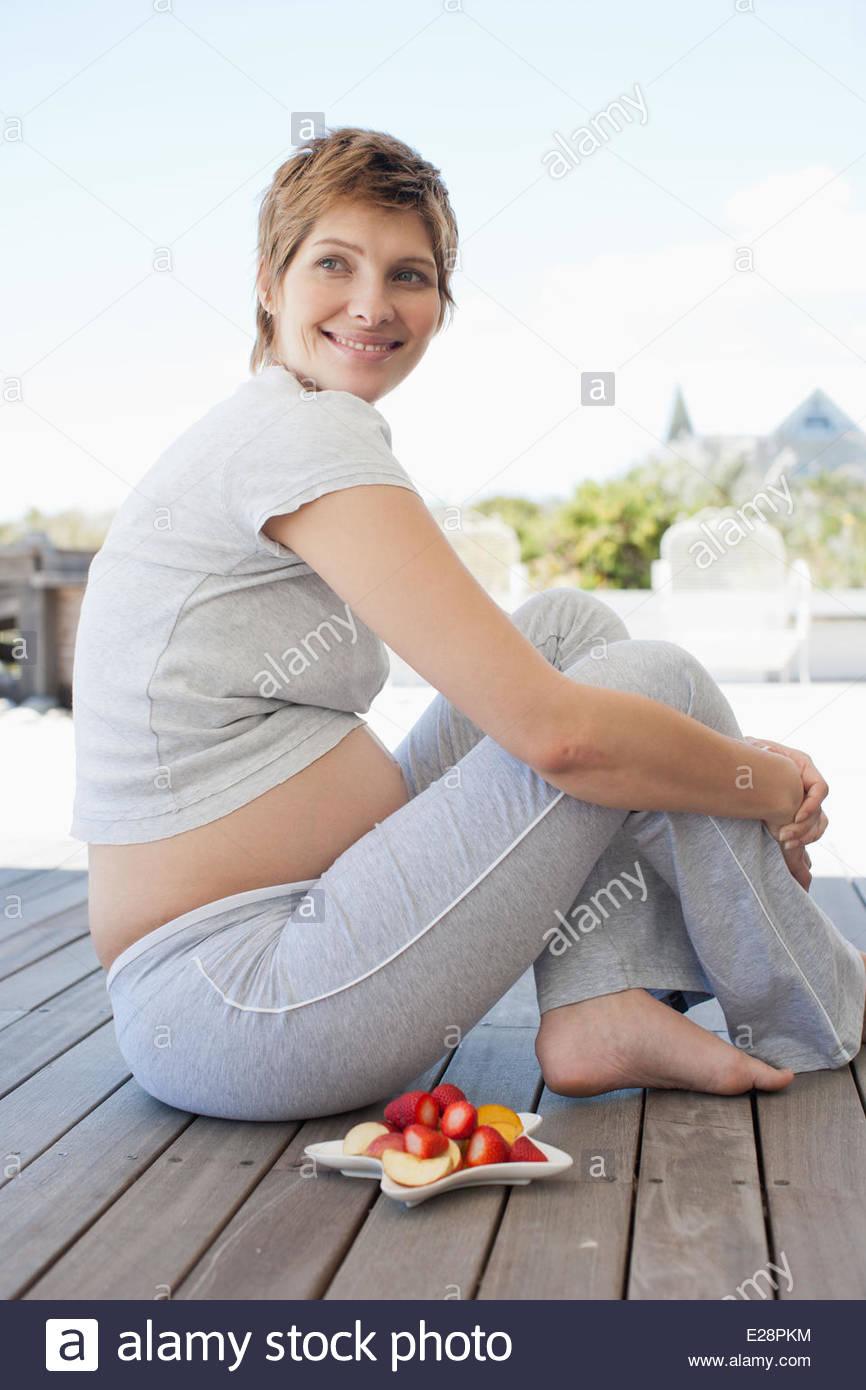 Donna incinta seduta sul ponte Immagini Stock
