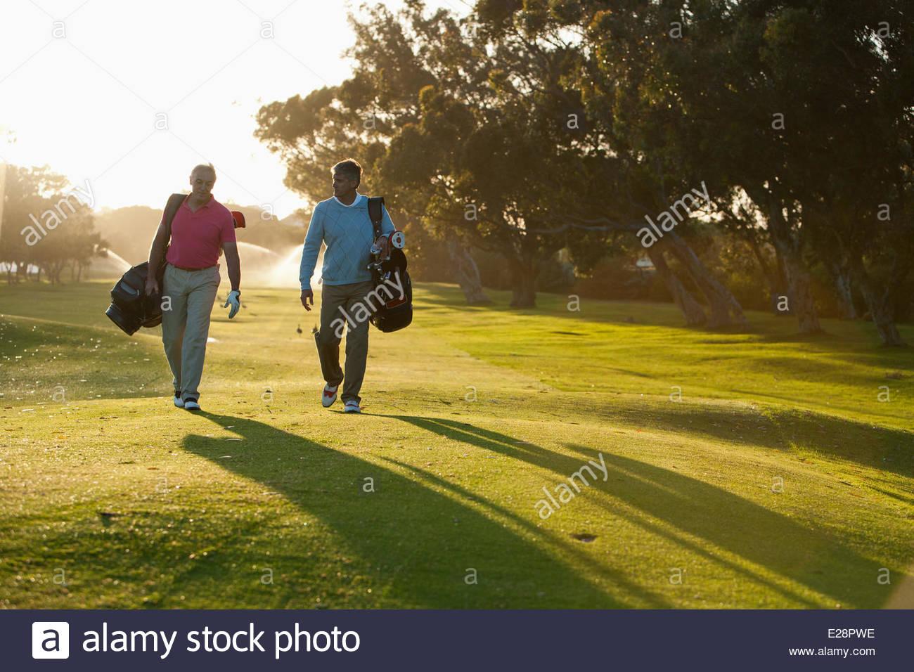 Gli uomini che trasportano le sacche da golf sul campo da golf Immagini Stock
