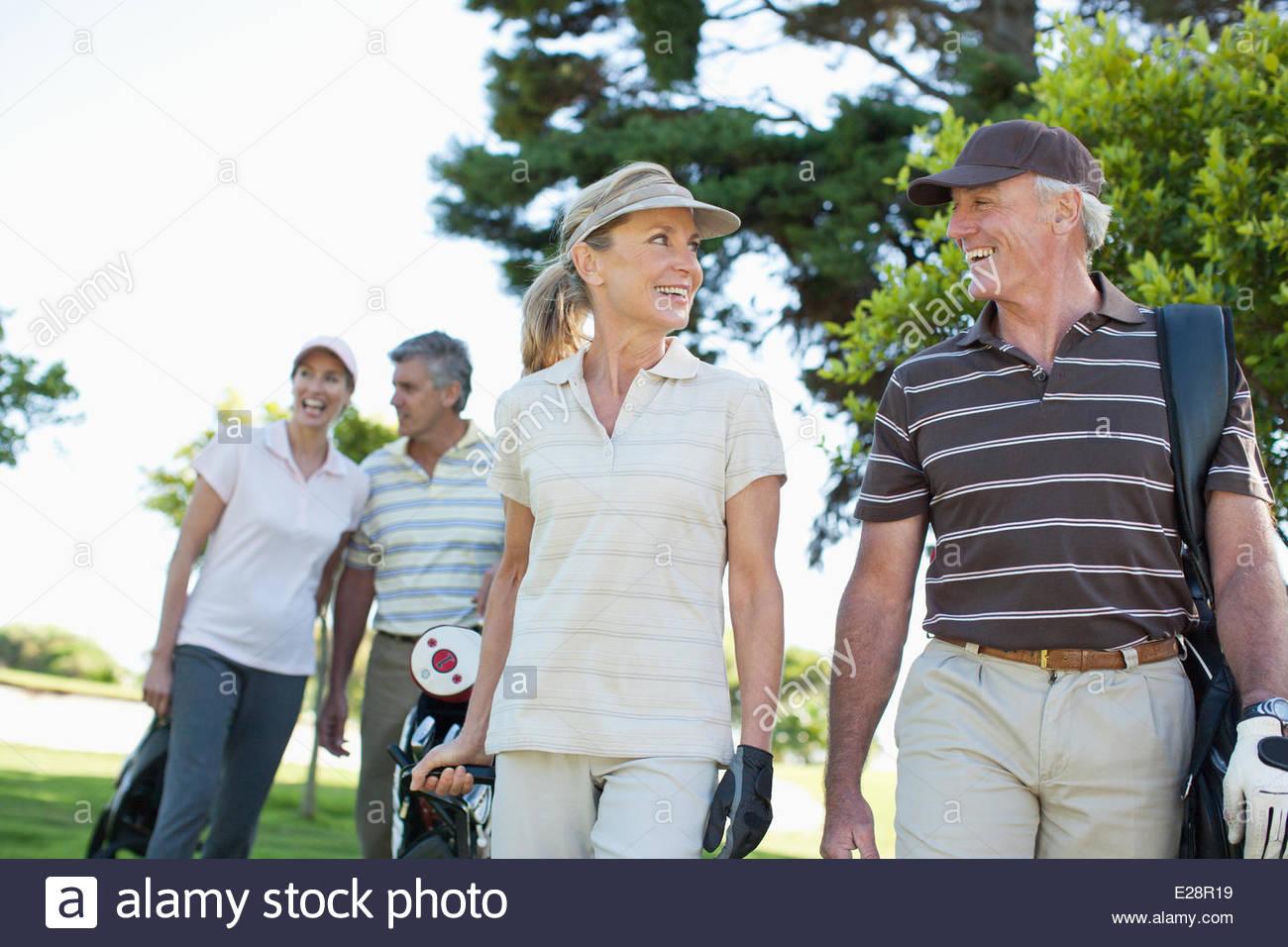 Coppia matura che trasportano le sacche da golf Immagini Stock