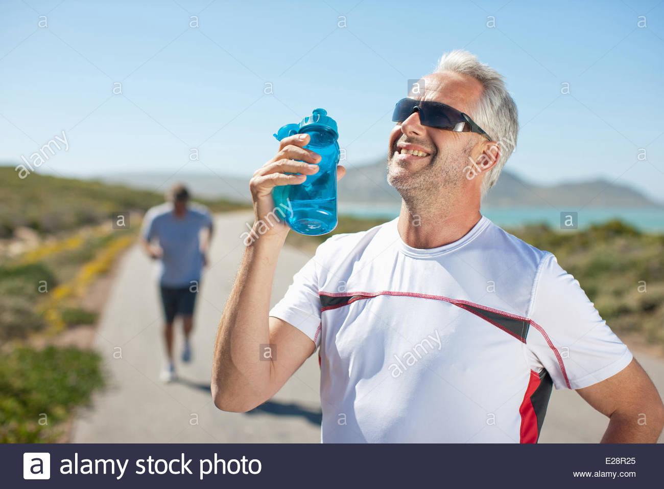 Uomo di bere dalla bottiglia di acqua su strada in remoto Immagini Stock