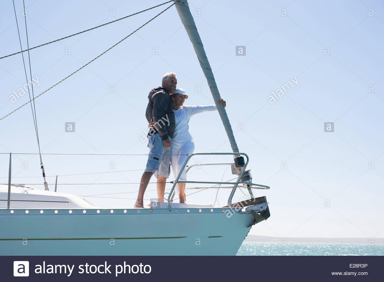 Coppia matura abbracciando sul ponte della barca a vela Immagini Stock